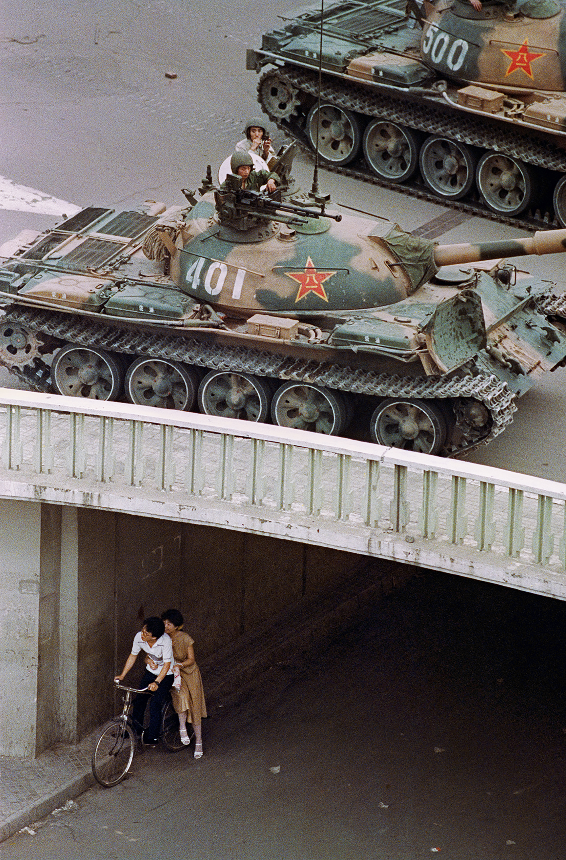 A young couple on a bicycle hide from Chinese soldiers in a tank overhead during the Tiananmen Square protests that were crushed June 4, 1989.
