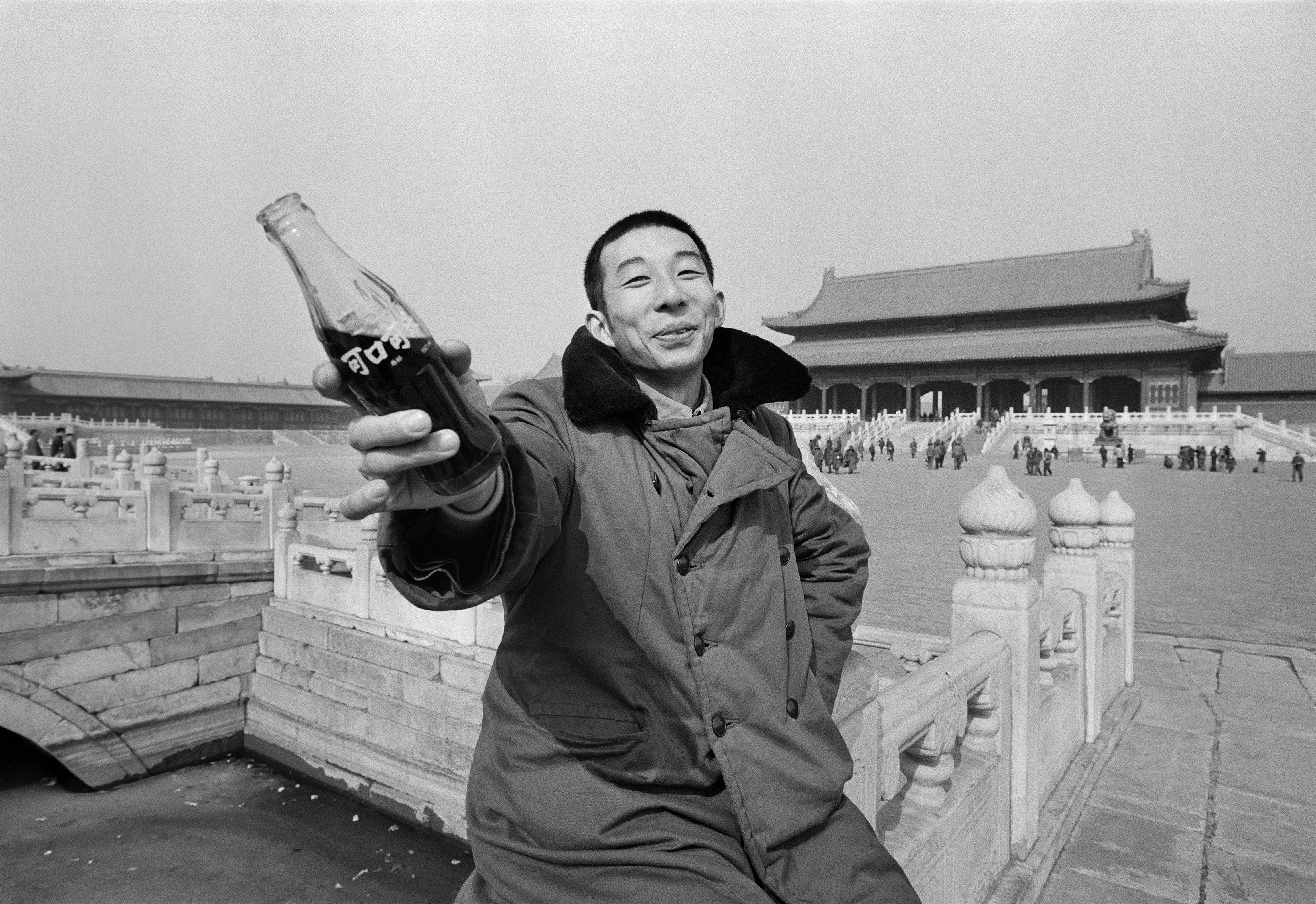 A young man holds a glass bottle of Coca-Cola, which had just resumed production in China, outside the Forbidden City, Beijing, 1981.