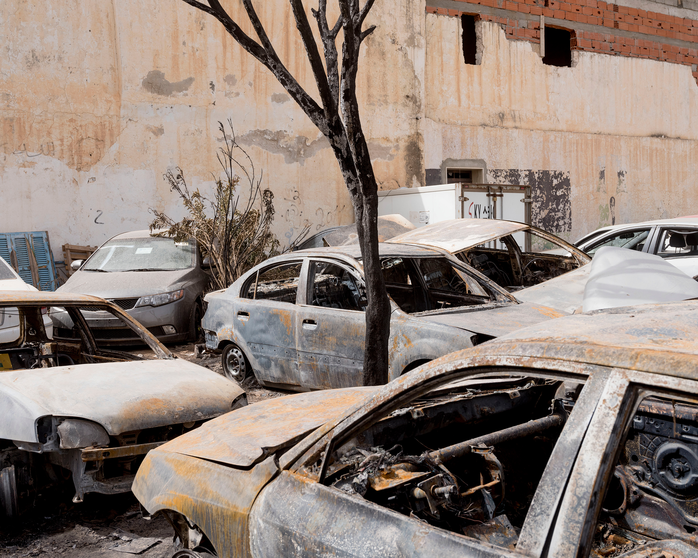 A group of vehicles, in a civilian area far from the fighting, that were burned after a GRAD rocket was launched by forces loyal to Haftar in Tripoli in April.