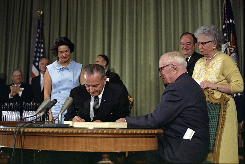 President Lyndon Johnson signing the Medicare bill, in Independence, Missouri, as Harry Truman looks on, July 30, 1965.