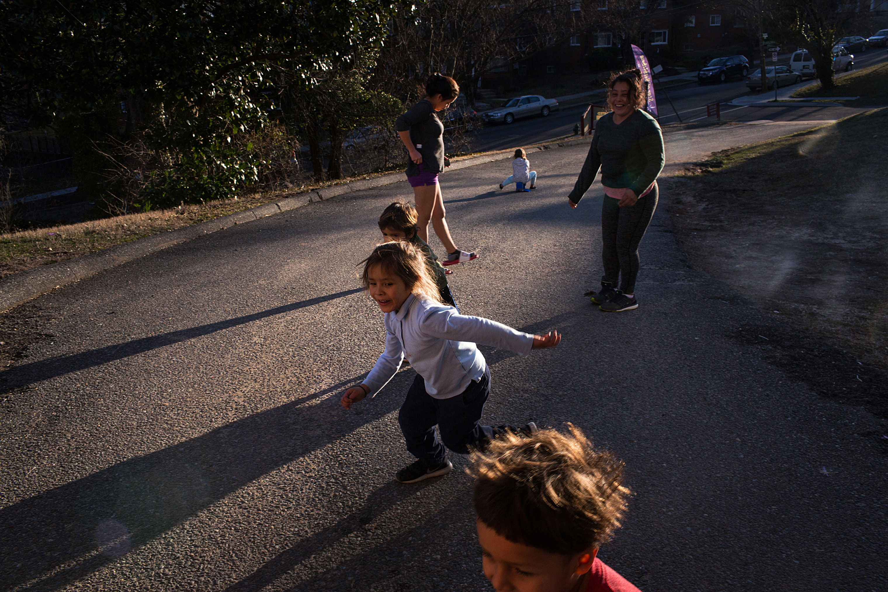 Maria, top-right, and Fanny play soccer with their respective children outside their house on March 12.