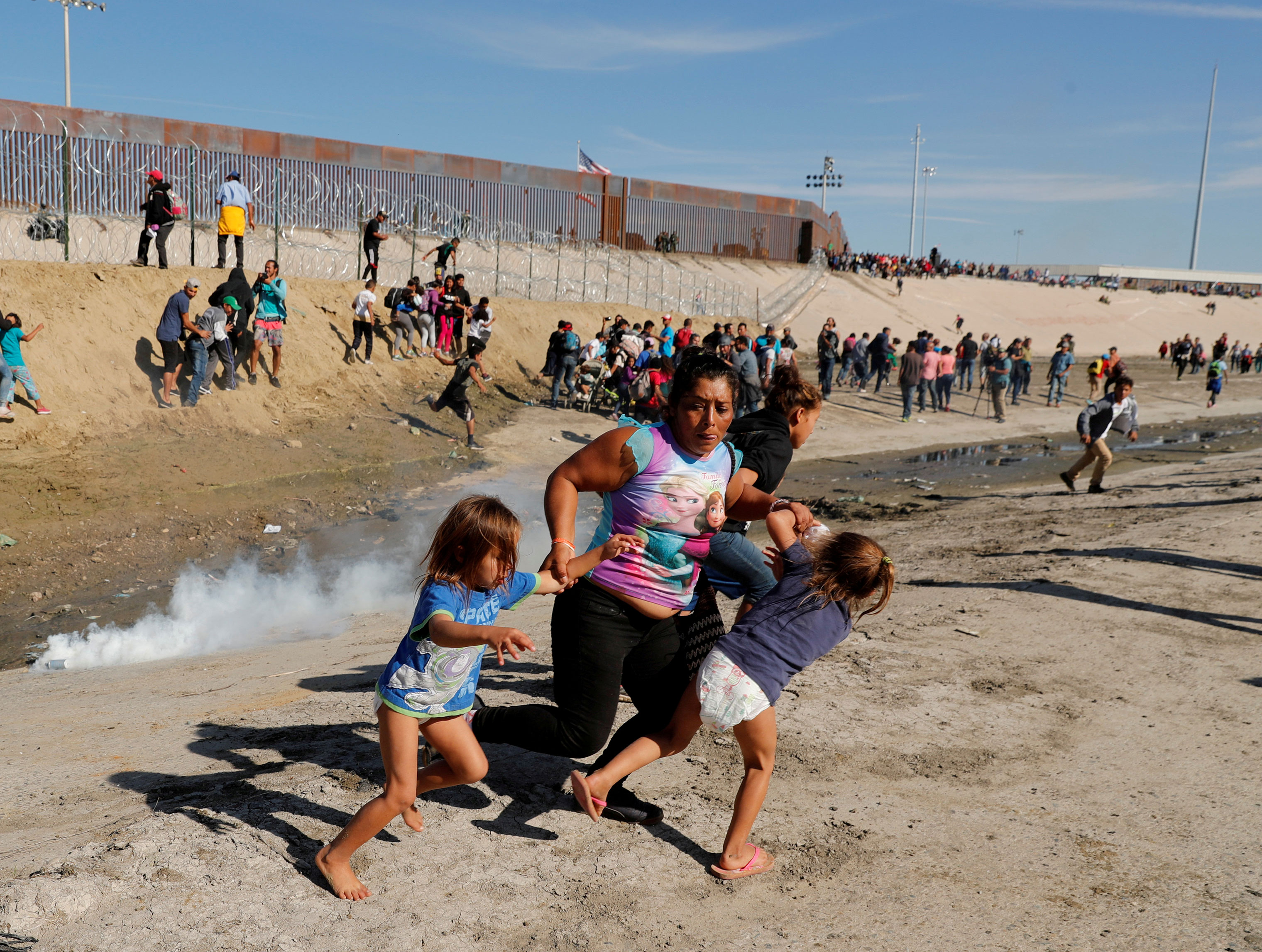 Castro runs away from tear gas with her five-year-old twin daughters Sayra Mavet Mejia Meza, left, and Cheyli Nallely Mejia Meza, right, in front of the border wall in Tijuana, Mexico, on Nov. 25, 2018.
