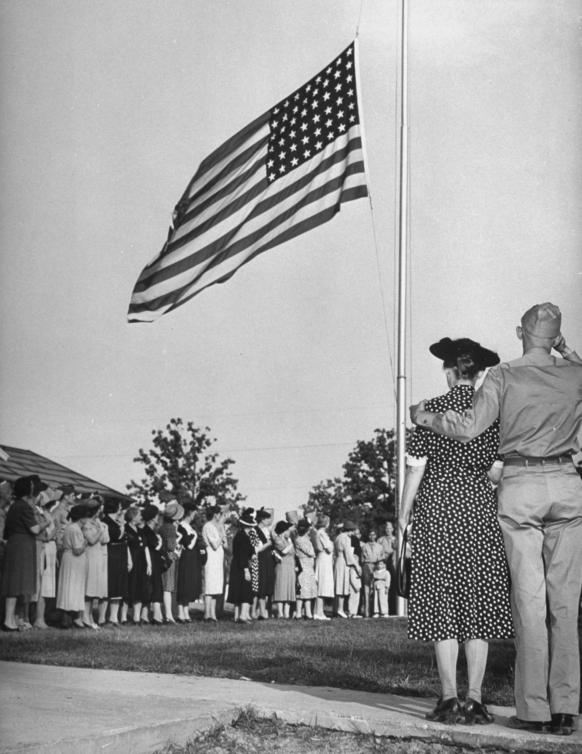 Mothers standing in line near the American flag during the crowing ceremonies of Mother's Day on a U.S. Army base. 1942.