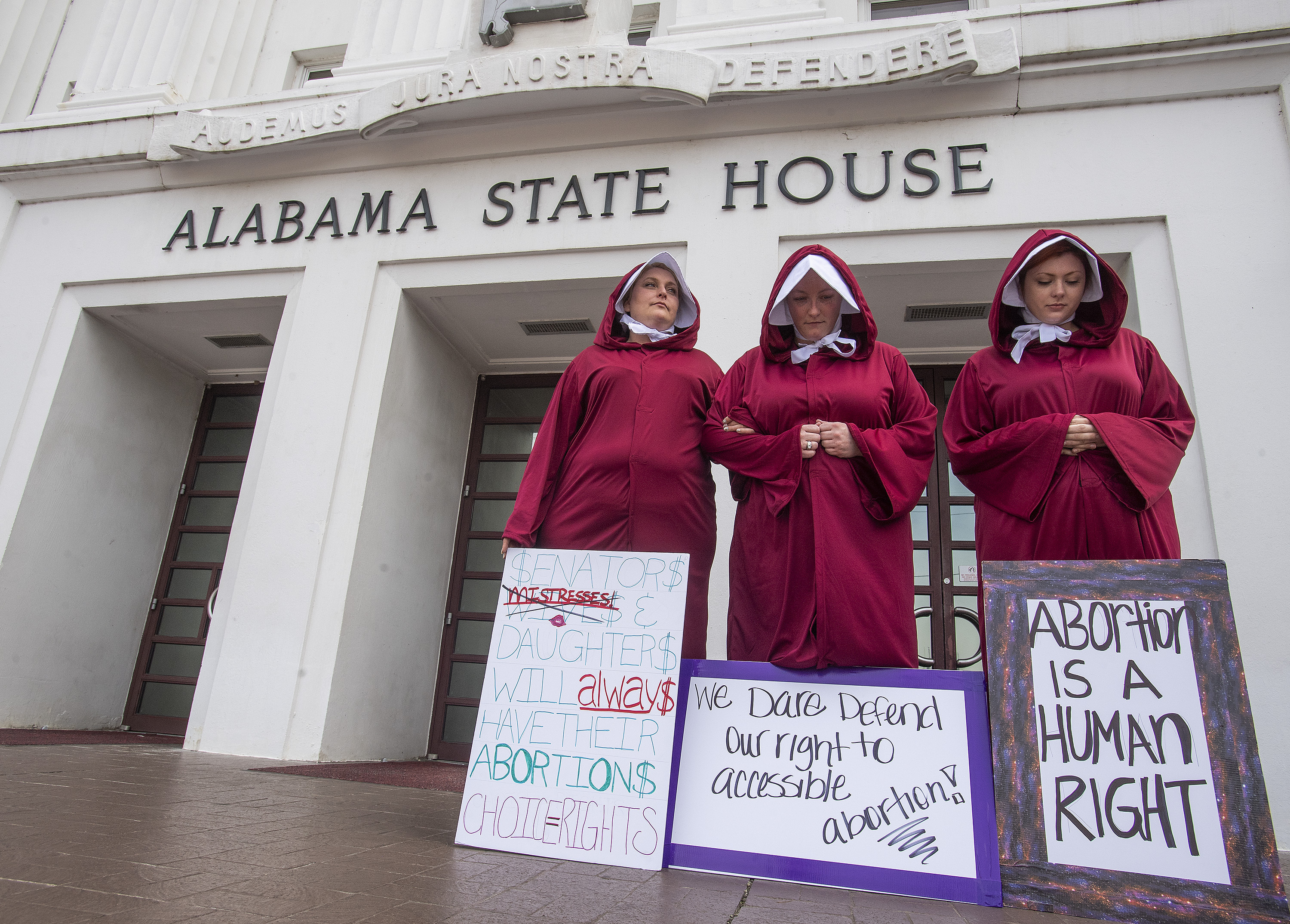 Bianca Cameron-Schwiesow, from left, Kari Crowe and Margeaux Hartline, dressed as handmaids, take part in a protest against HB314, the abortion ban bill, at the Alabama State House in Montgomery, Ala., on Wednesday April 17, 2019. (Mickey Welsh/The Montgomery Advertiser via AP)