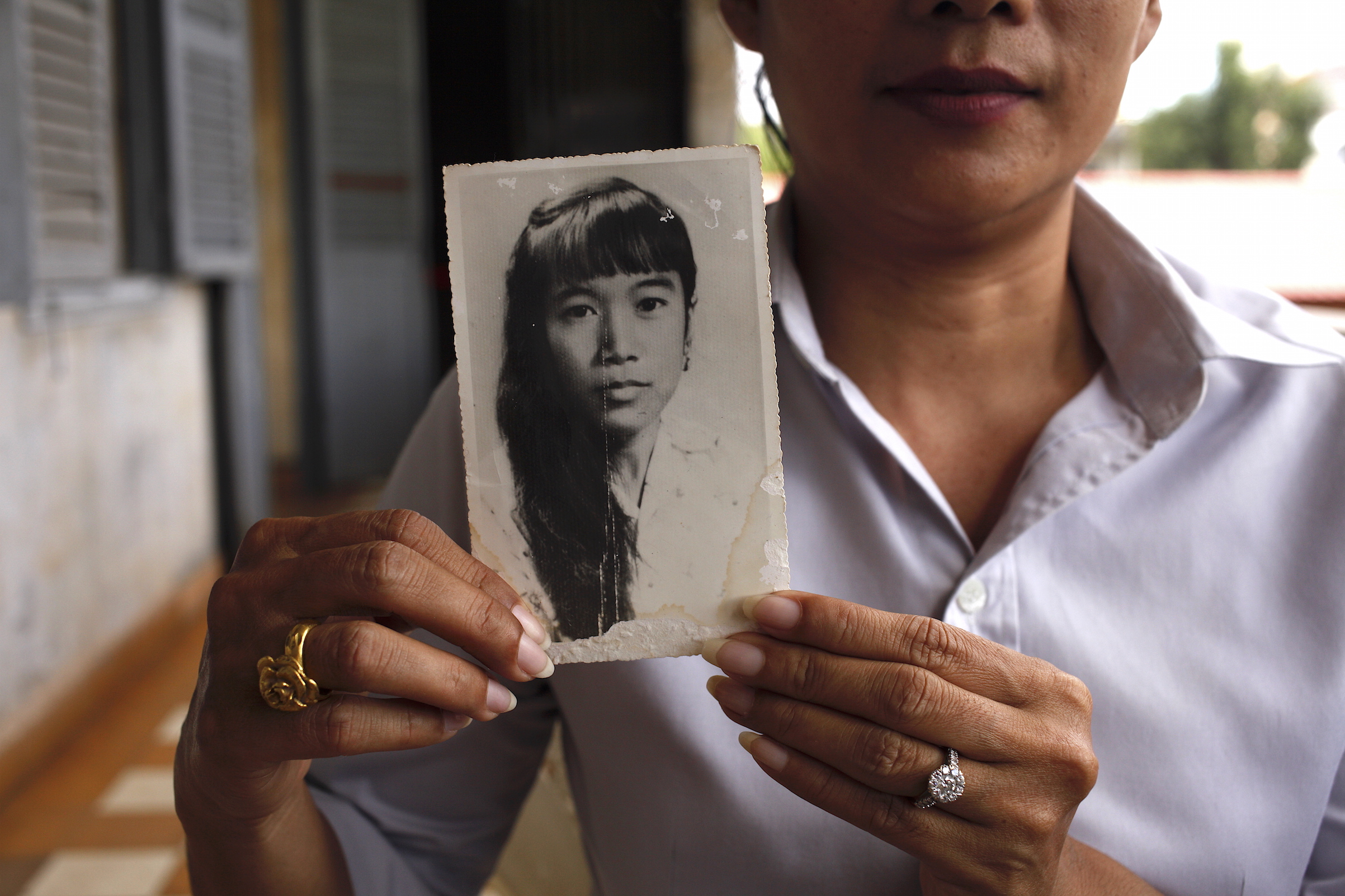 Chheng Samin was born under a pagoda shortly after the fall of Phnom Penh. She holds a picture of her mother, Chheng Samit, who survived the Khmer Rouge but died young. She now works at Tuol Sleng.
