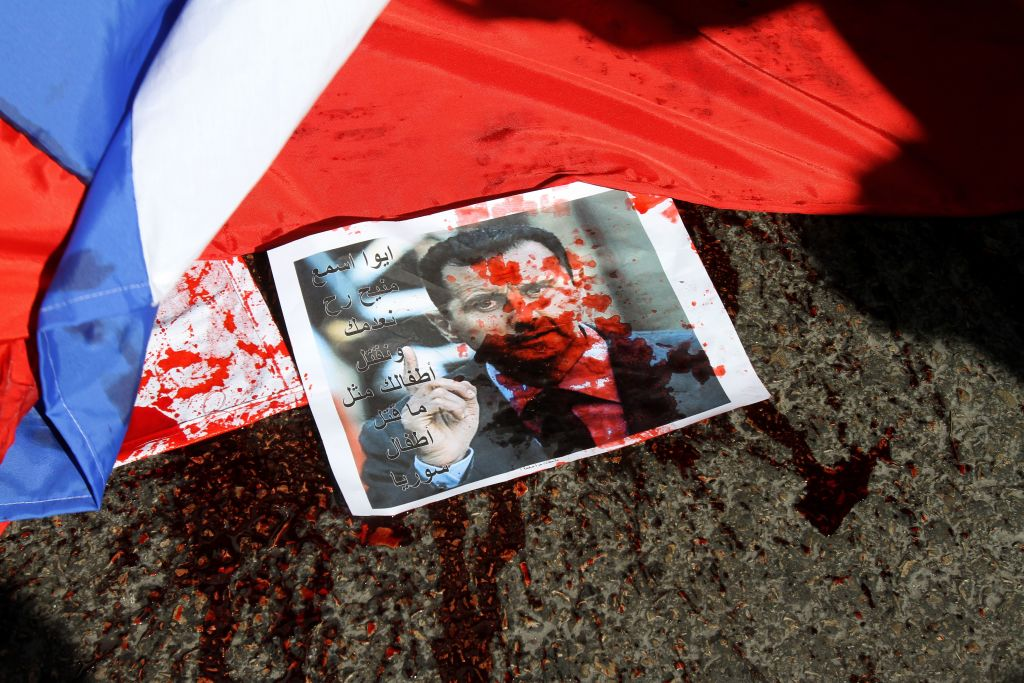 A picture of Syria's embattled President Bashar Assad sprayed with red paint lies on the ground next to a Russian flag about to be set on fire by protesters opposed to the Syrian regime during a demonstration outside the Russian embassy in Beirut on February 5, 2012.