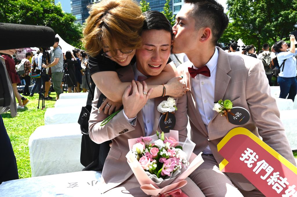 Shane Lin (C) is comforted by his partner Marc Yuan (R) and a friend during a wedding ceremony in Shinyi district in Taipei on May 24, 2019.