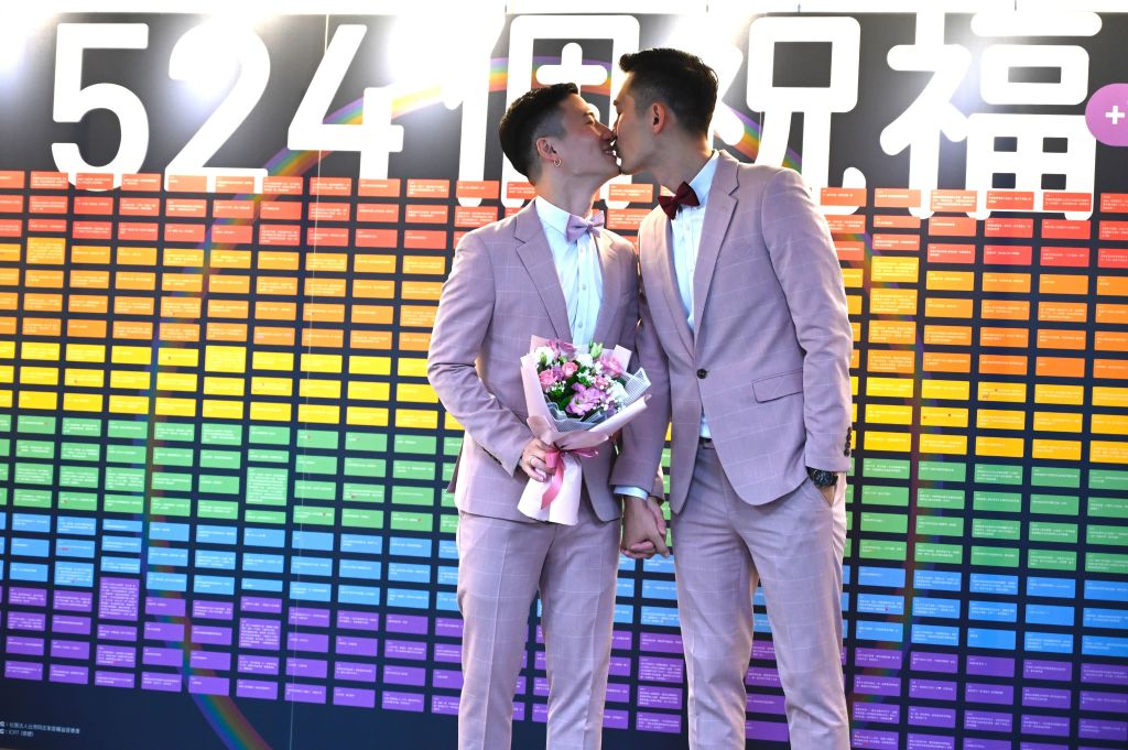 Taiwan's first gay couple Shane Lin (L) and Marc Yuan kiss outside the Household Registration Office in Shinyi district in Taipei on May 24, 2019.