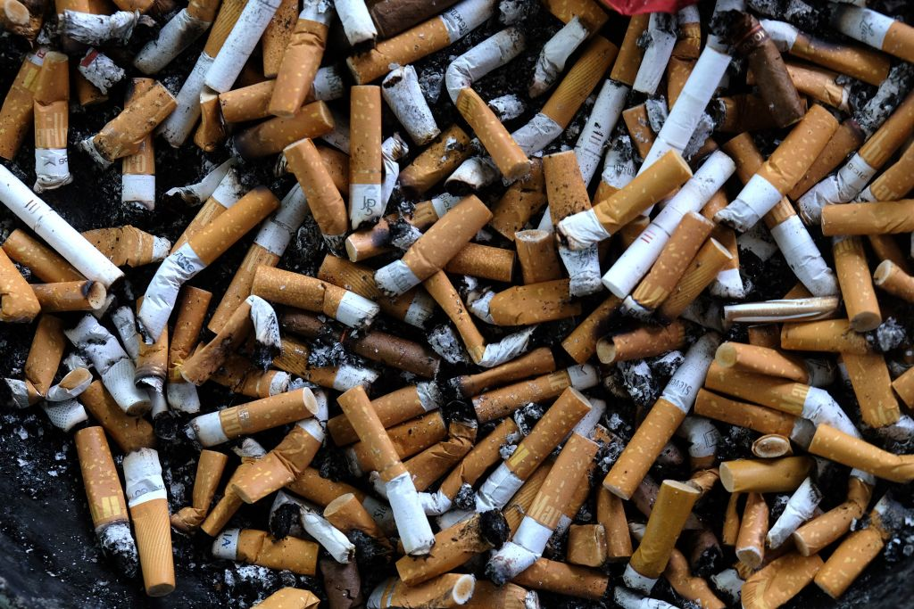An ashtray filled with cigarettes butts on an outdoor smoking stand.