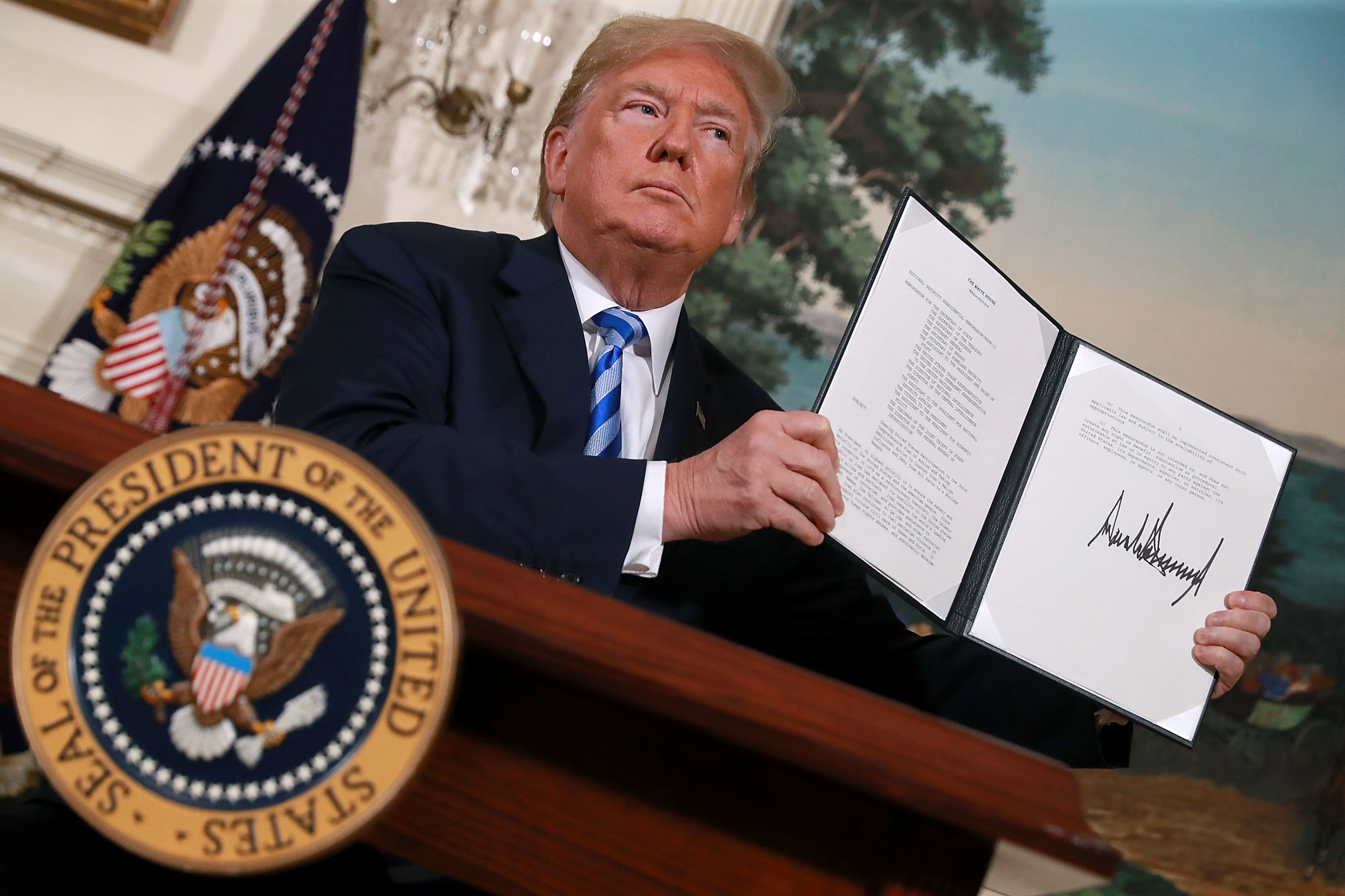 President Donald Trump holds up a memorandum that reinstates sanctions on Iran after he announced his decision to withdraw the United States from the 2015 Iran nuclear deal, on May 8, 2018, in Washington, D.C.