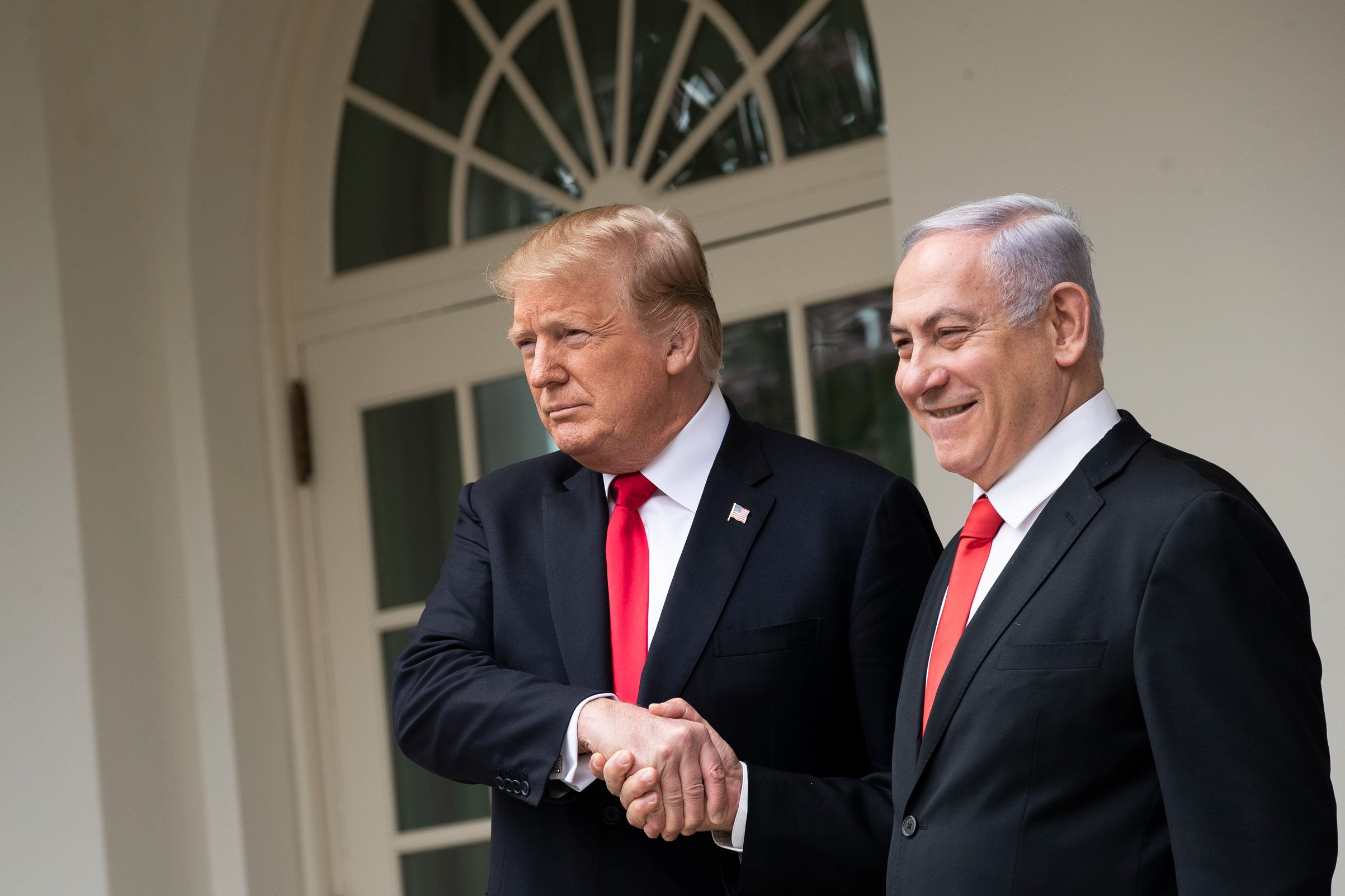 President Donald Trump and Prime Minister of Israel Benjamin Netanyahu shake hands while walking through the colonnade prior to an Oval Office meeting at the White House March 25, 2019 in Washington, D.C.
