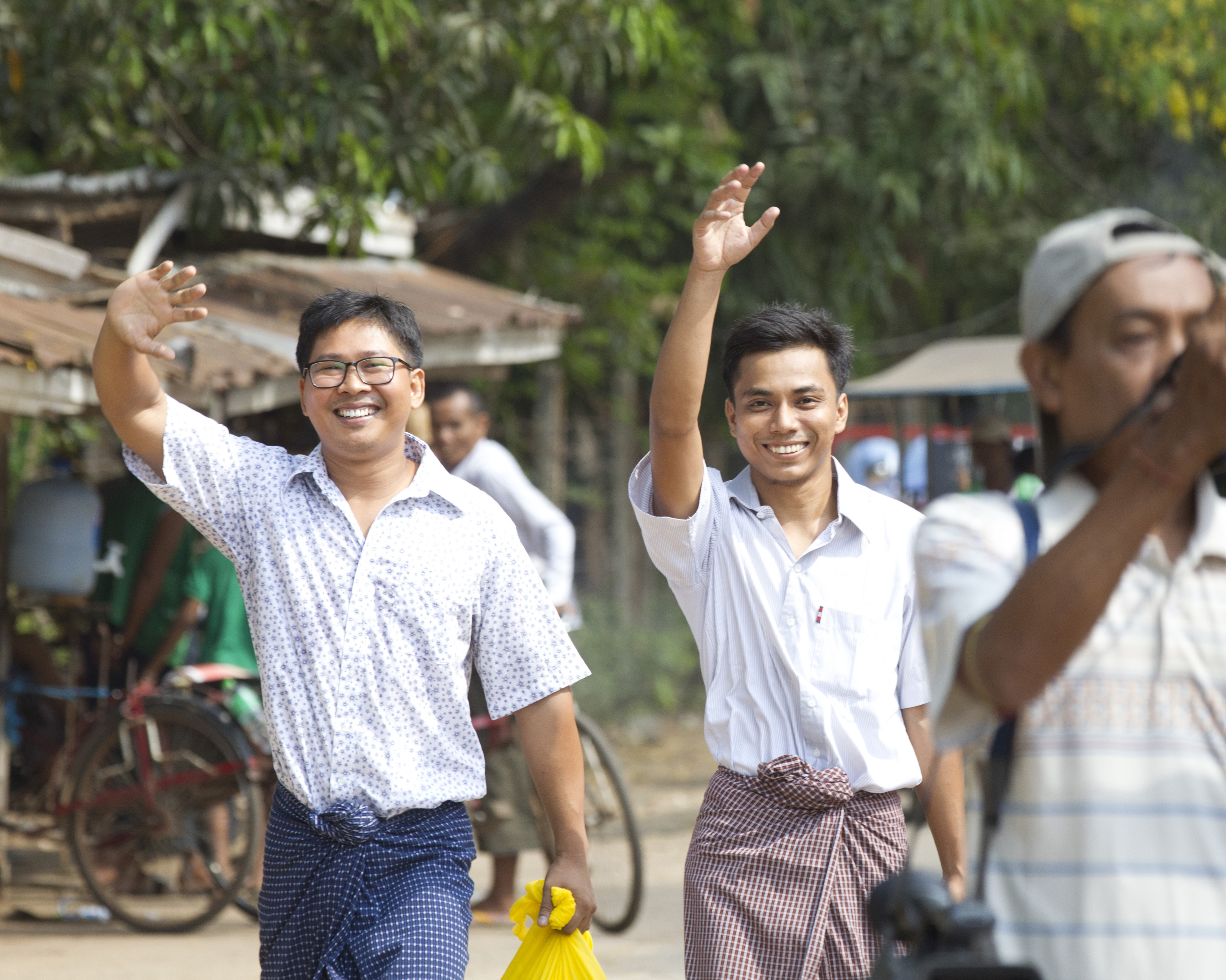 Reuters journalists Wa Lone, left, and Kyaw Soe Oo, right, wave as they walk out from Insein Prison after being released in Yangon, Myanmar on May 7, 2019.
