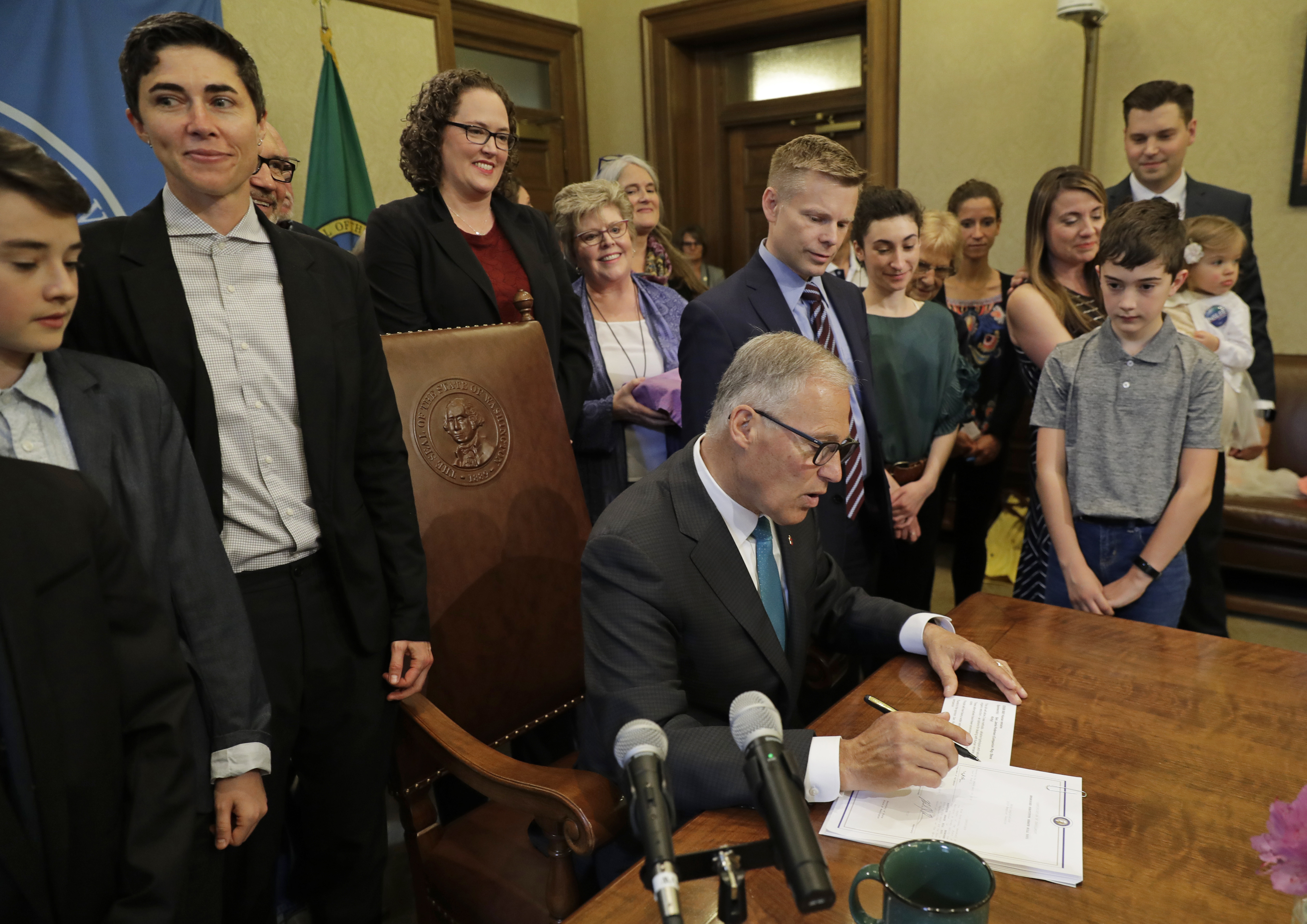 Katrina Spade, upper left, the founder and CEO of Recompose, looks on May 21, 2019, as Washington Gov. Jay Inslee, center, signs a bill into law that allows licensed facilities to offer 'human composting' services.