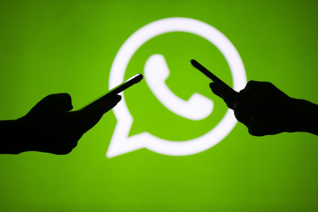 People hold mobile phones in front of the logo of WhatsApp application in Ankara, Turkey on July 18, 2018.