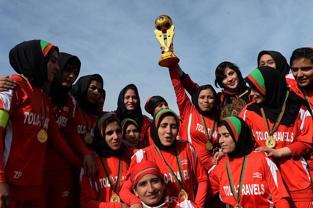 Afghan female football players from Afghan team celebrate with the trophy after their women's football tournament final match against Isteghlal in Kabul on December 6, 2013.