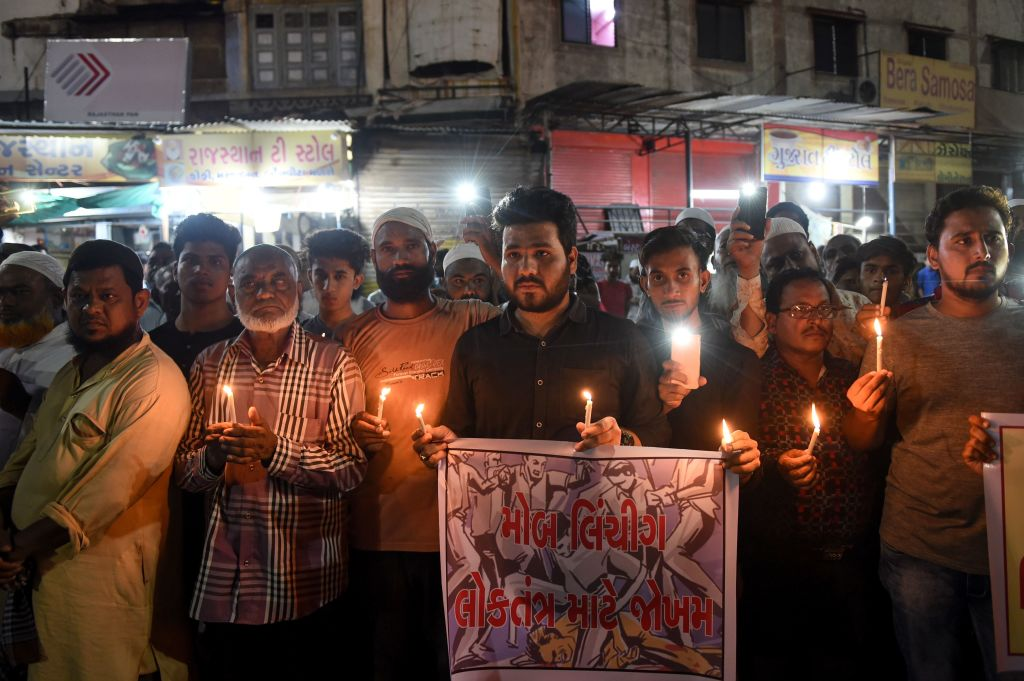 Indian Muslims holding candles and posters as they participate in a protest against the mob lynching of Tabrez Ansari in the Jharkhand state, in Ahmedabad on June 27, 2019.