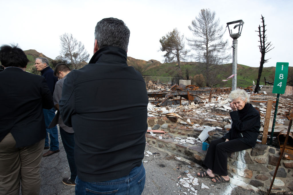 Marsha Maus, 75, right, a 15-year resident of Seminole Springs Mobile Home Park in Agoura Hills, sits next to a destroyed home as Gov. Jay Inslee of Washington talks with the media while touring Seminole Springs after devastating wildfires on March 11, 2019 in Agoura Hills, California.