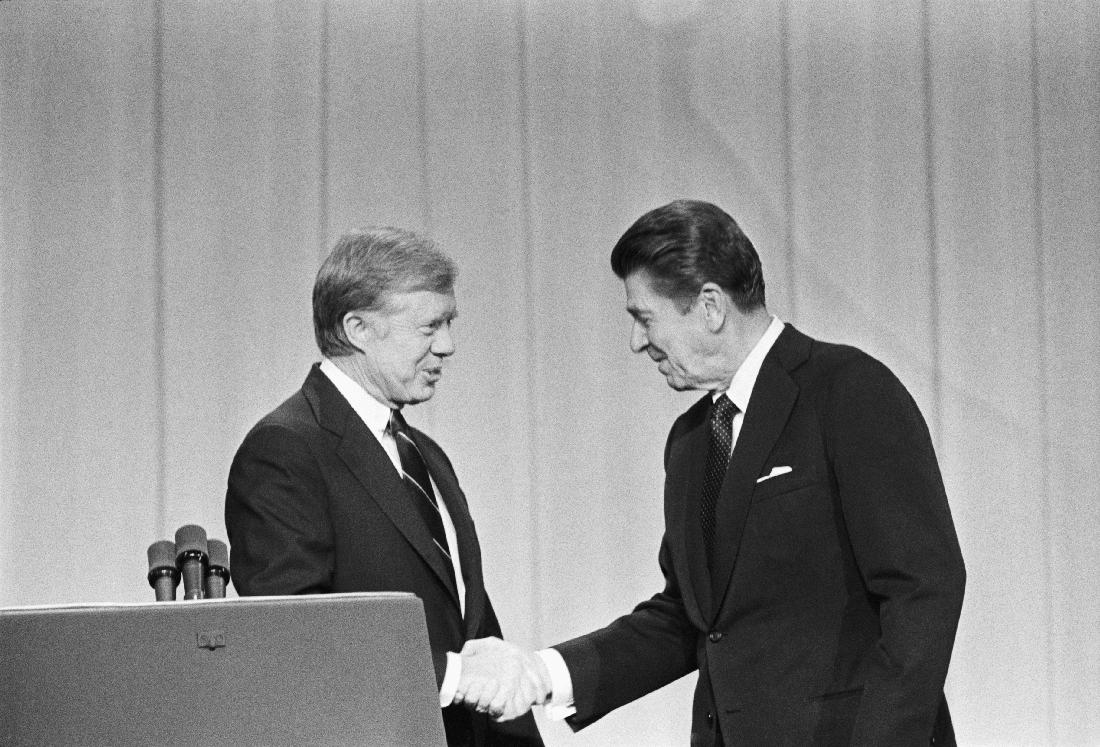 President Jimmy Carter and his Republican challenger, Ronald Reagan, shake hands as they greet one another before their debate on the stage of the Music Hall in Cleveland, Ohio.