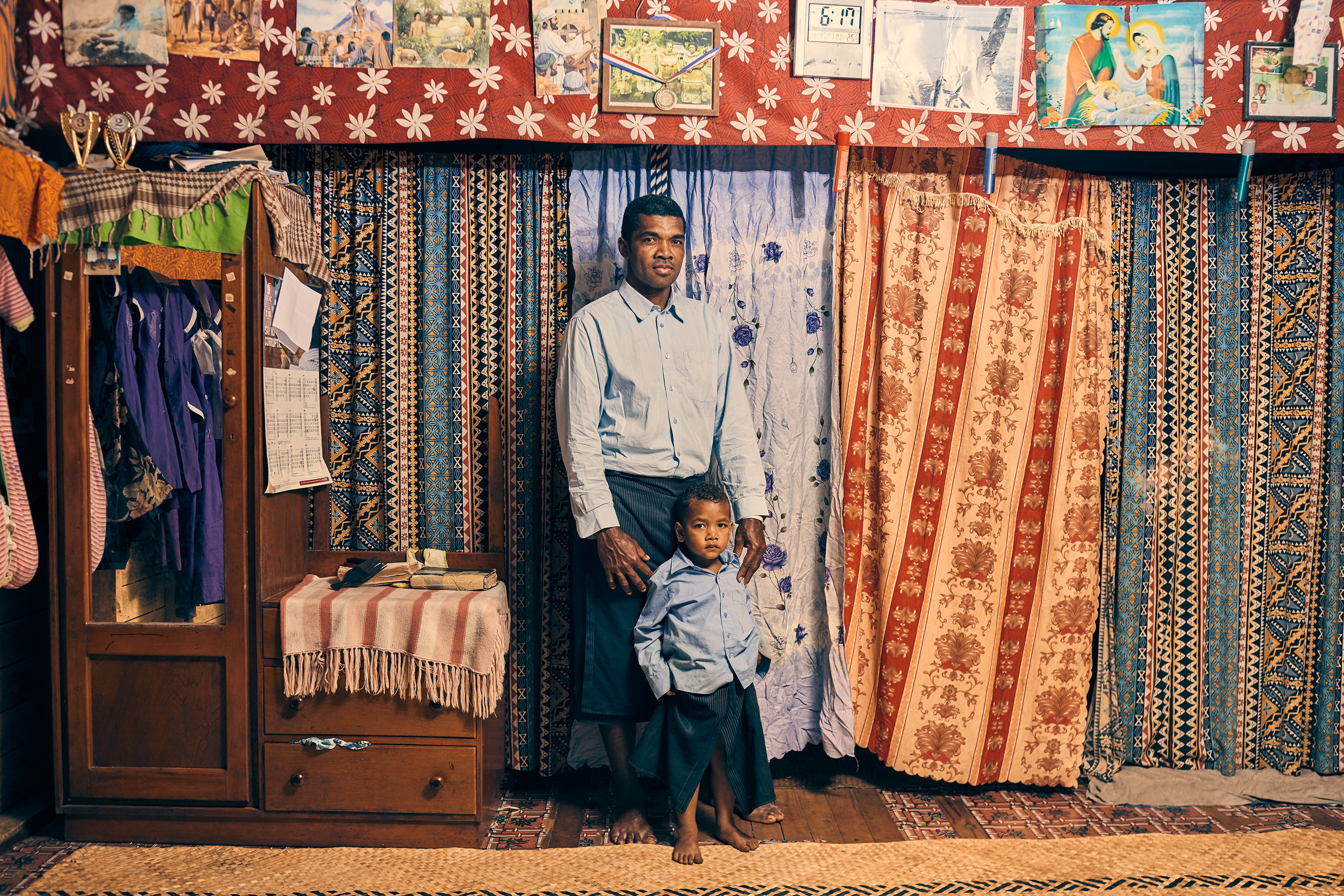 Apisai Logaivau and his son Simione Botu in their home in the relocated village. Logaivau lives here with his wife and four other children.