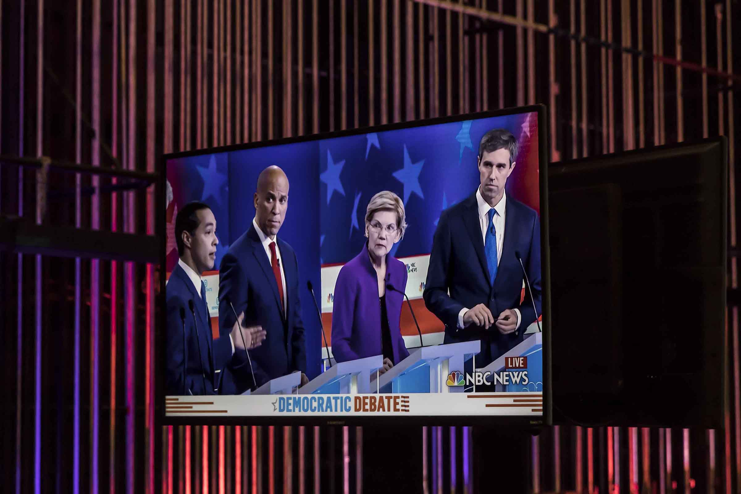 Democratic presidential hopefuls (L-R) former housing secretary Julian Castro, Sen. Cory Booker (D-NJ), Sen. Elizabeth Warren (D-MA), former Texas congressman Beto O'Rourke are shown on a screen in the spin room during the first Democratic primary debate of the 2020 presidential campaign season hosted by NBC News at the Adrienne Arsht Center for the Performing Arts in Miami, Florida, June 26, 2019.
