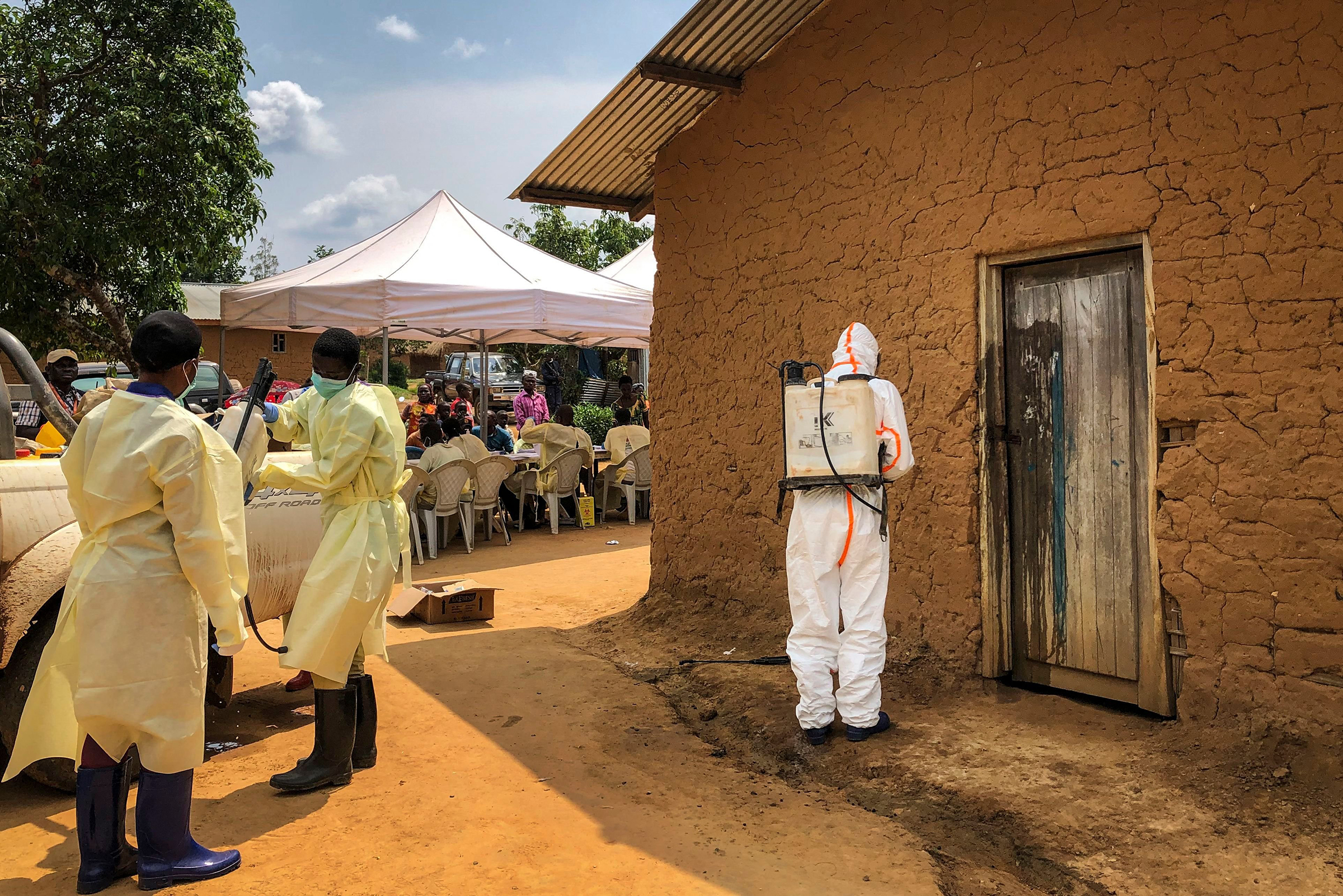 A worker from the World Health Organization (WHO) decontaminates the doorway of a house on a plot where two cases of Ebola were found, in the village of Mabalako, in eastern Congo.