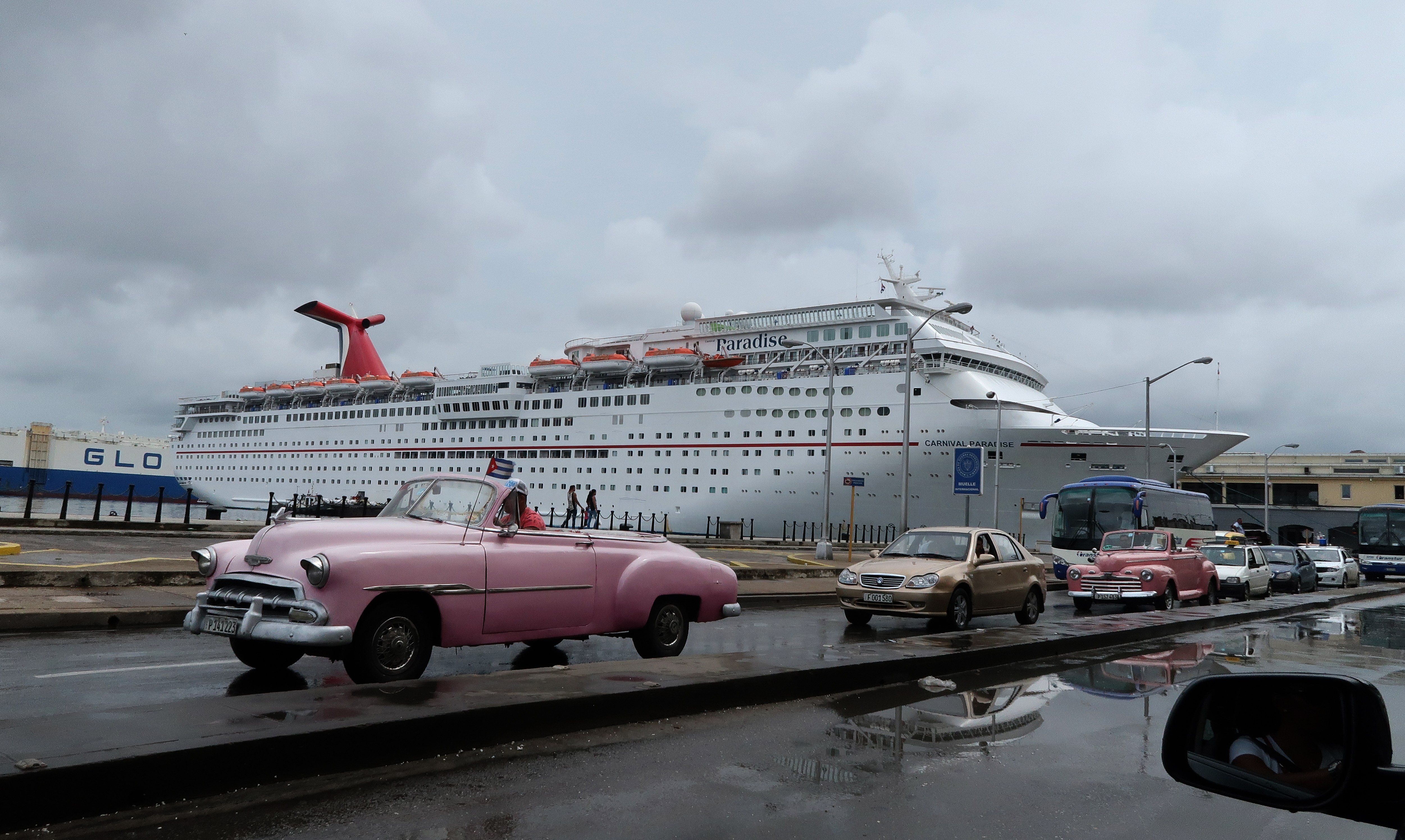 A classic car taxi drives past a cruise ship in port on October 12, 2017 in Havana, Cuba.