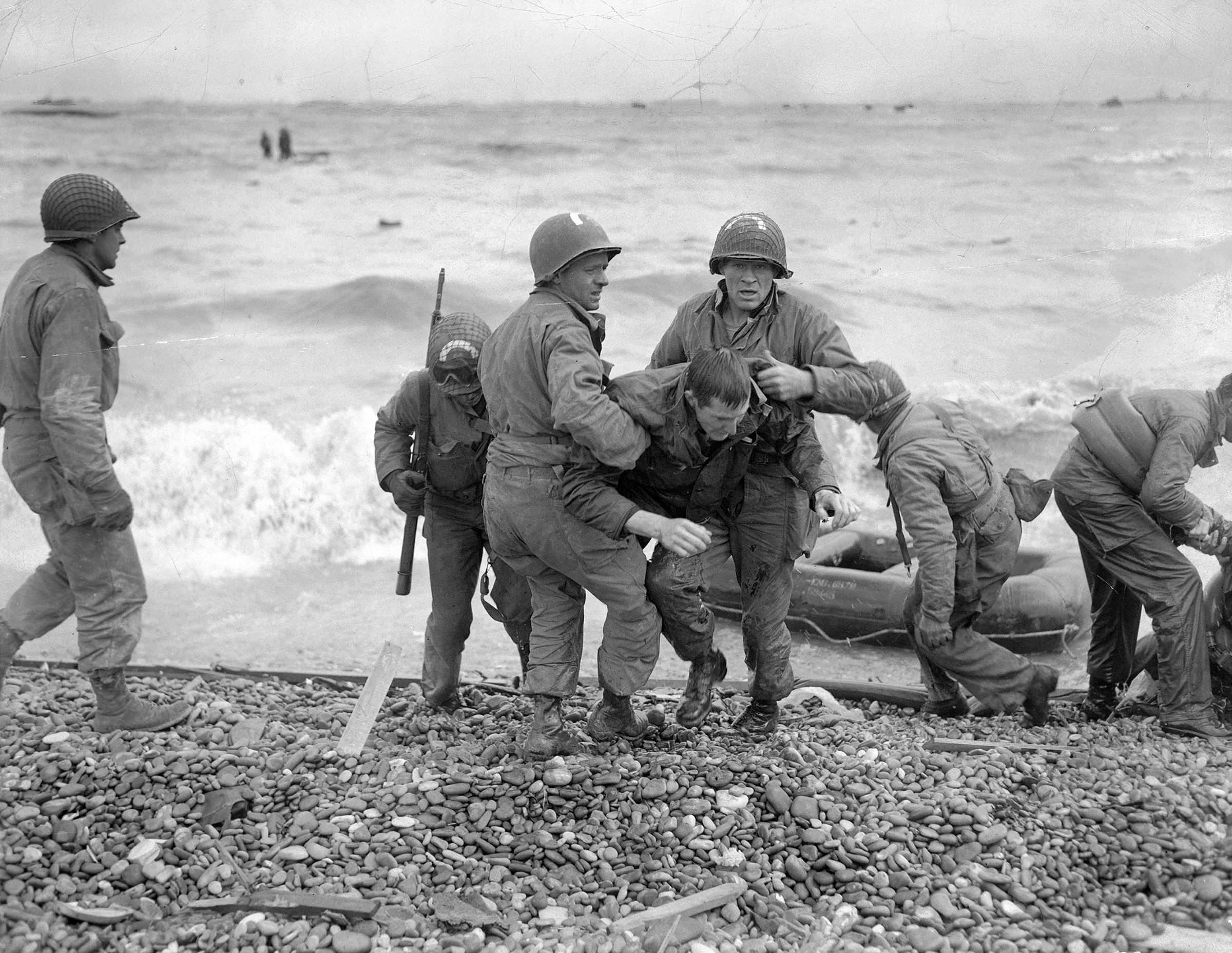 Members of an American landing party help soldiers ashore near Cherbourg, France, after their landing craft was sunk by enemy action on June 6, 1944.