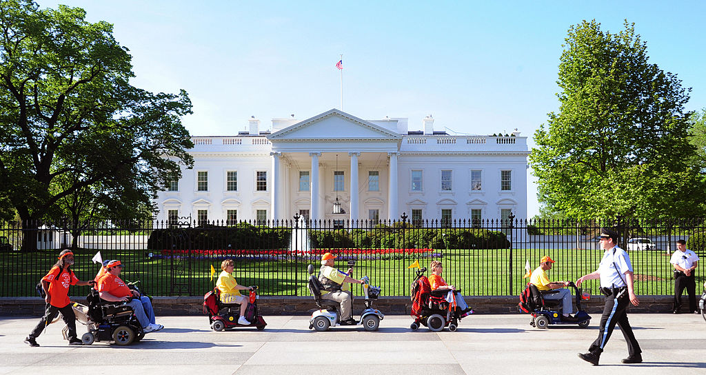 Members of ADAPT, a disability rights group pass the White House during a protest April 27, 2009 in Washington, DC.