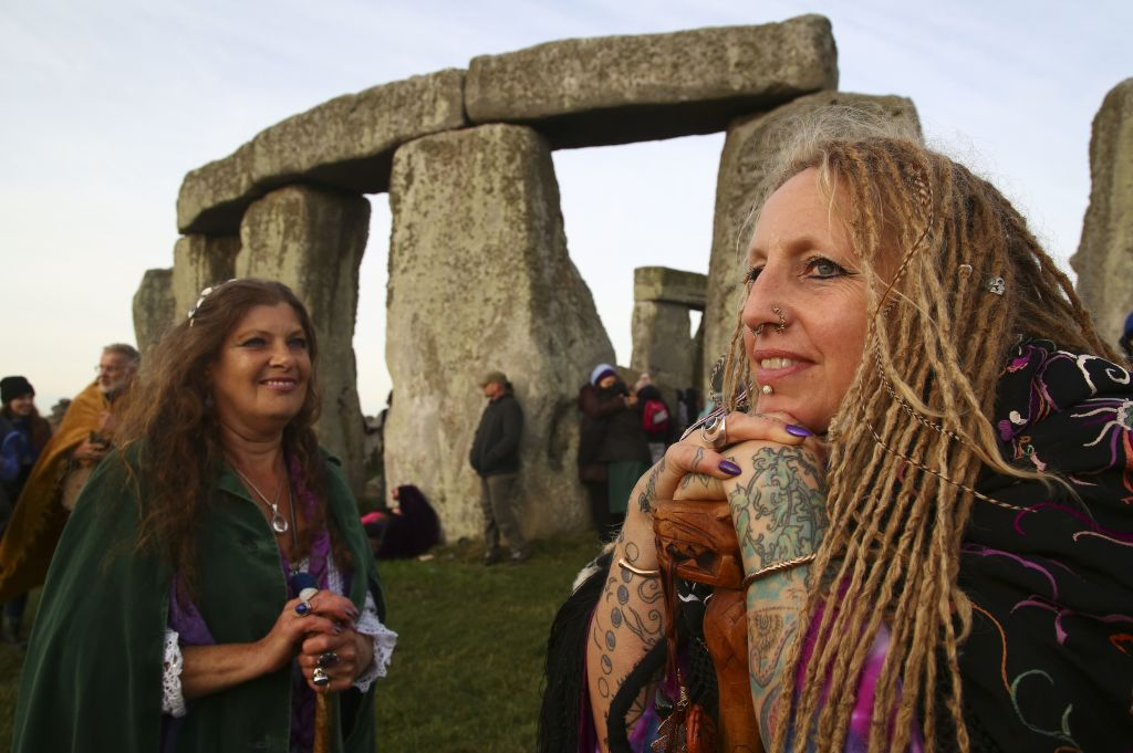 Revellers watch the sunrise as they celebrate the Pagan festival of summer solstice at Stonehenge in Wiltshire, England on June 21, 2018.