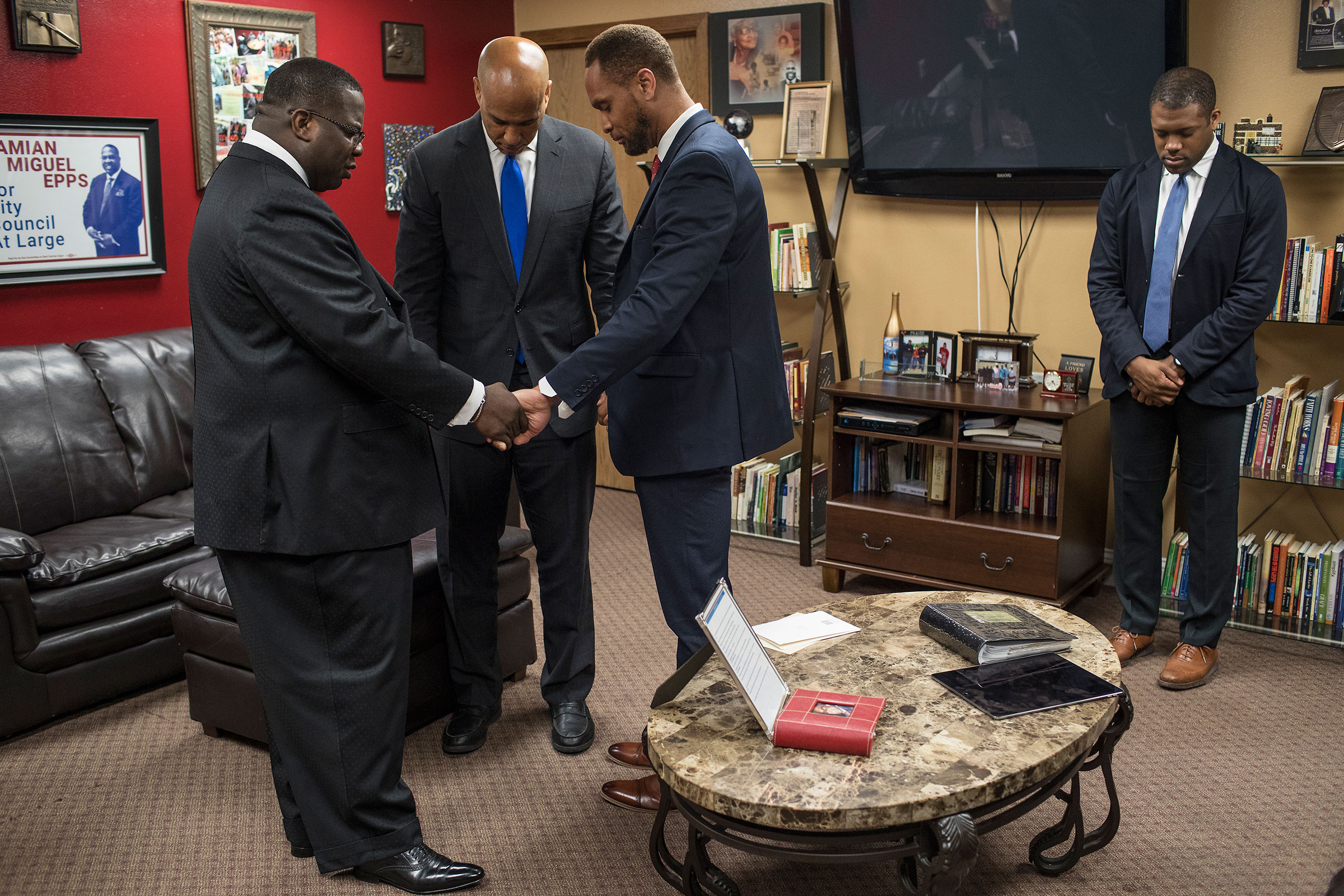 Pastor Dr. Damian Miguel Epps, Senator Cory Booker, and Linn County Supervisor Stacey Walker pray before the Youth Empowerment Day service at Mt. Zion Missionary Baptist Church in Cedar Rapids, Iowa on June 9.