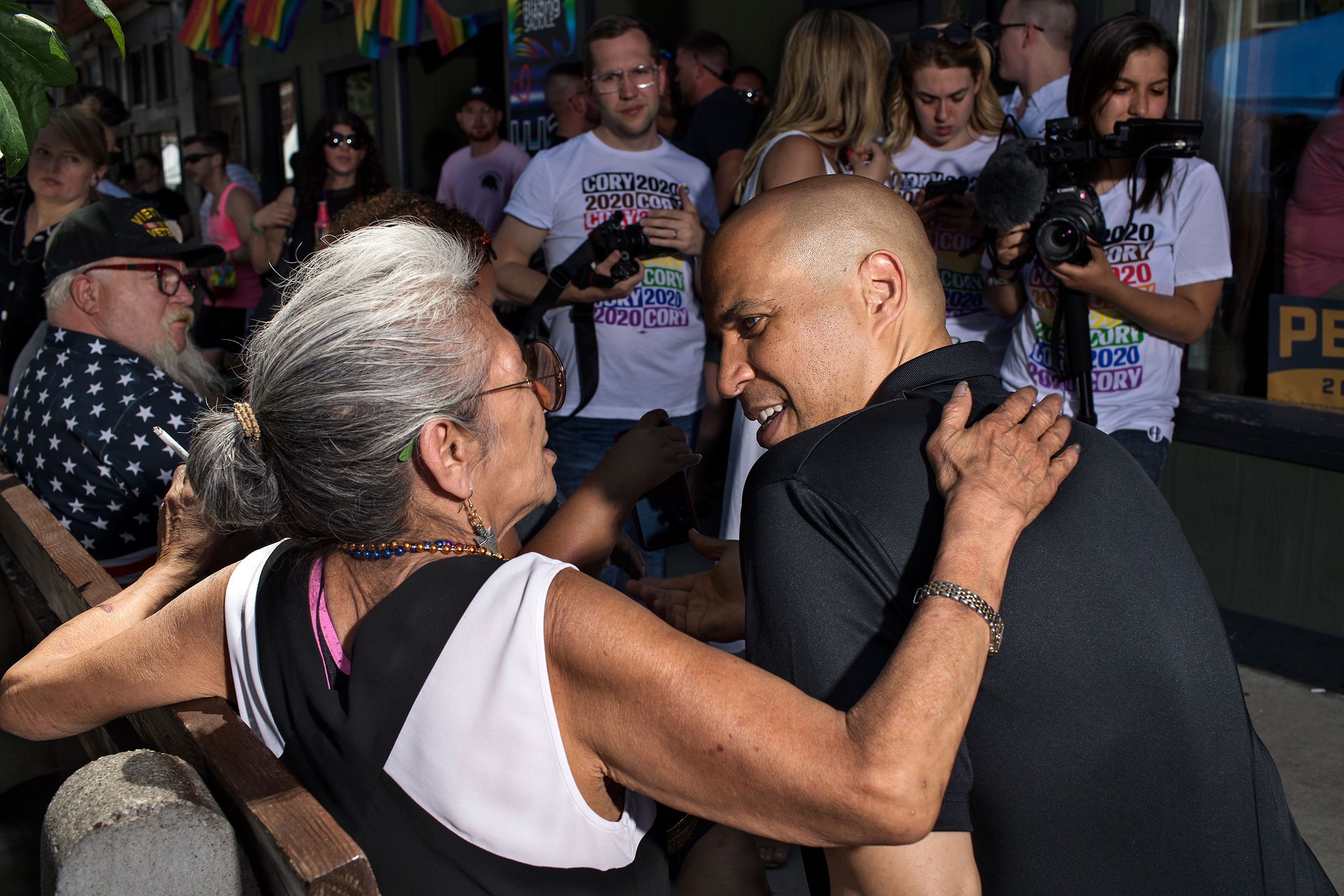 Booker speaks with a community member in Des Moines' East Village neighborhood during the Capital City Pride Festival on June 8.
