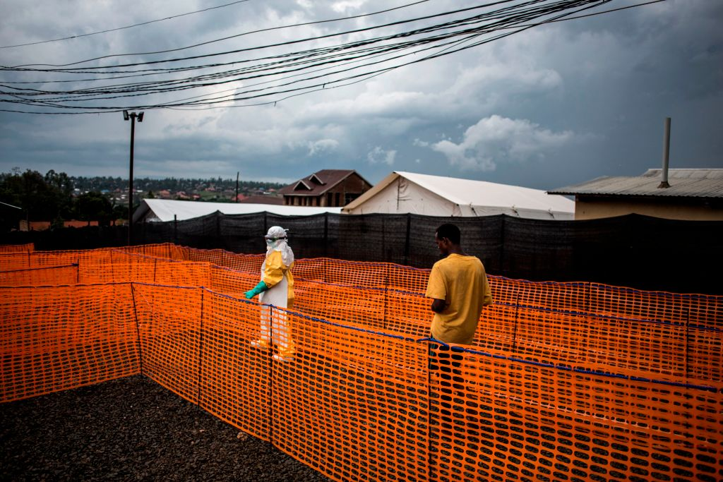 A health worker escorts a new unconfirmed Ebola patient to his room at a newly build MSF (Doctors Without Borders) supported Ebola treatment centre (ETC) on November 7, 2018 in Bunia, Democratic Republic of the Congo.
