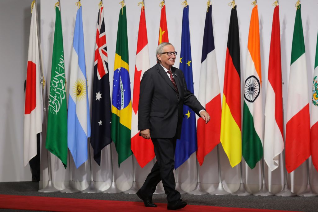 President of the European Commission Jean-Claude Juncker walks past G20 member flags as he is welcomed by Japan's Prime Minister Shinzo Abe to the G20 Summit in Osaka on June 28, 2019. (Photo by Ludovic MARIN / POOL / AFP)        (Photo credit should read LUDOVIC MARIN/AFP/Getty Images)