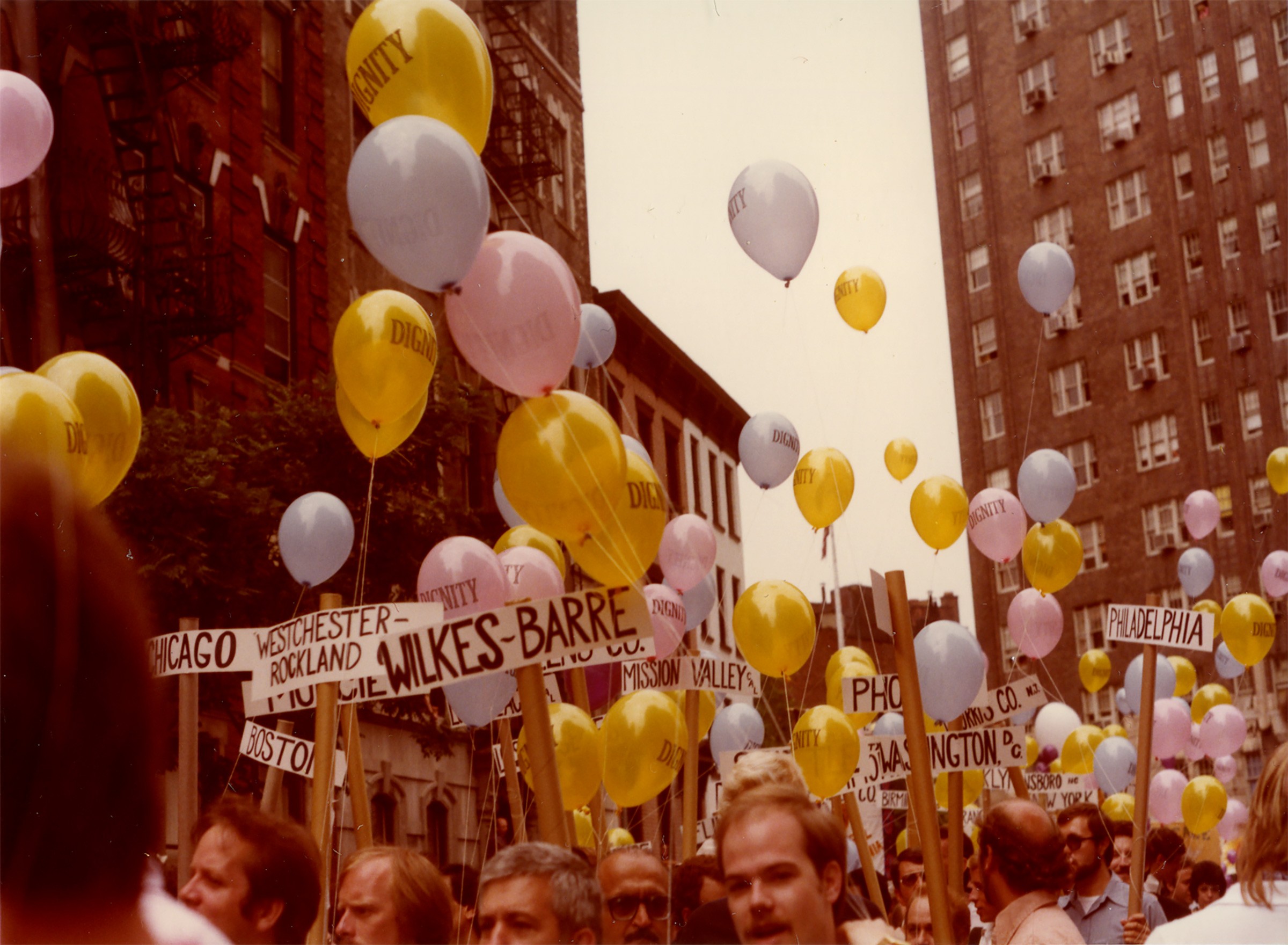 People march with balloons saying DIGNITY and picket signs that indicate place of origin, 1980