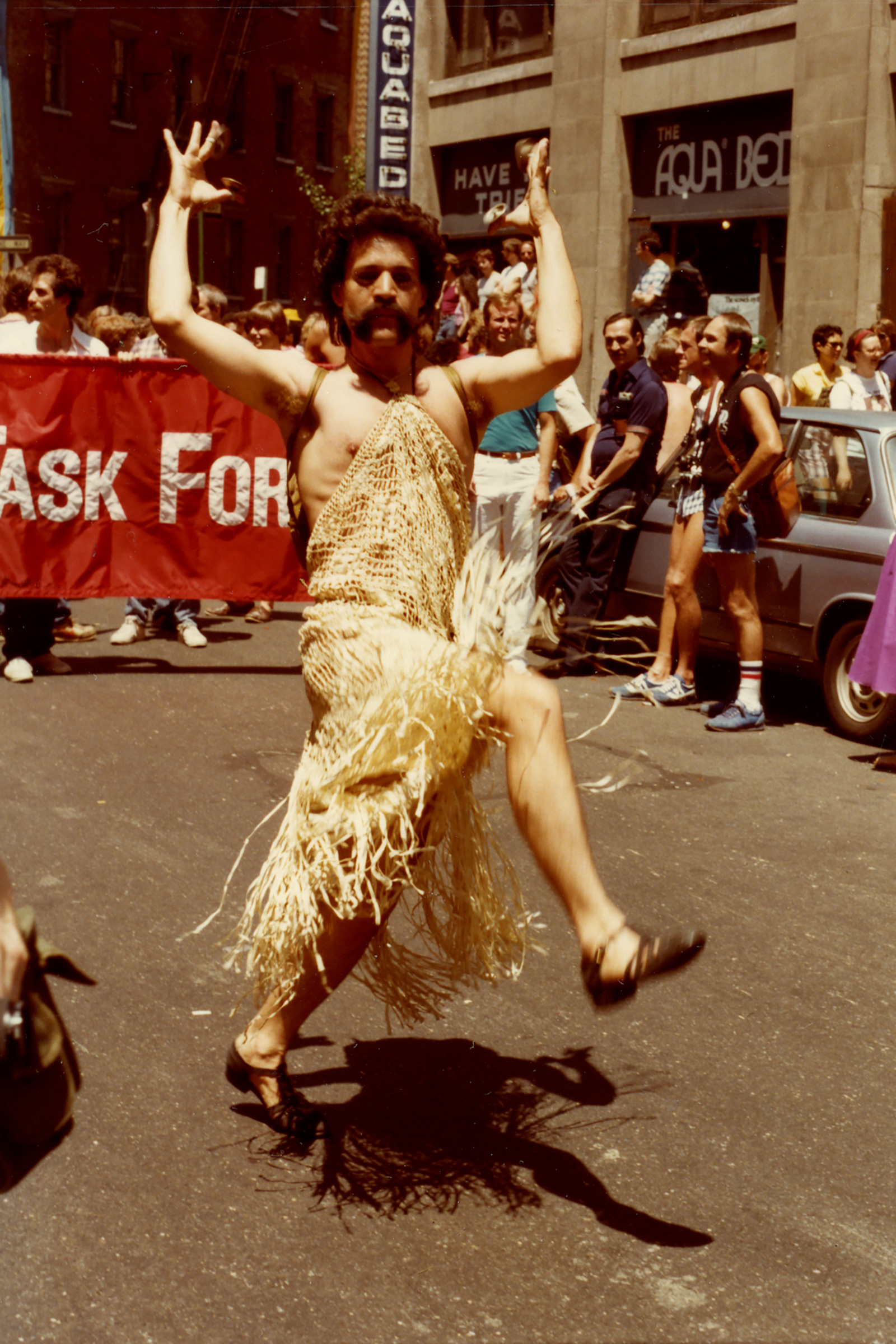 A person in a gold dress marches during the Pride Parade in 1981.