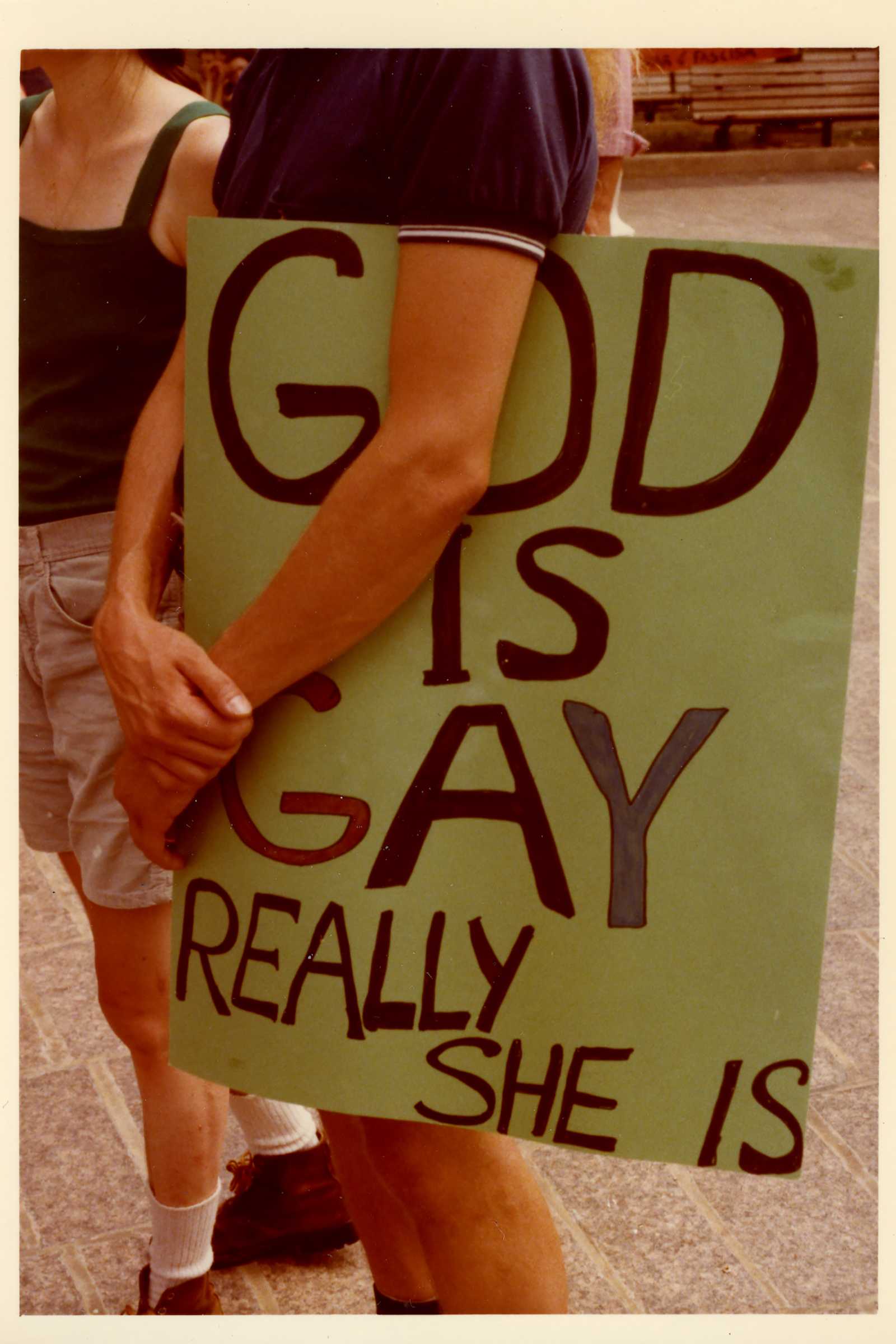 A person holds a sign that reads God is Gay Really She Is, 1977