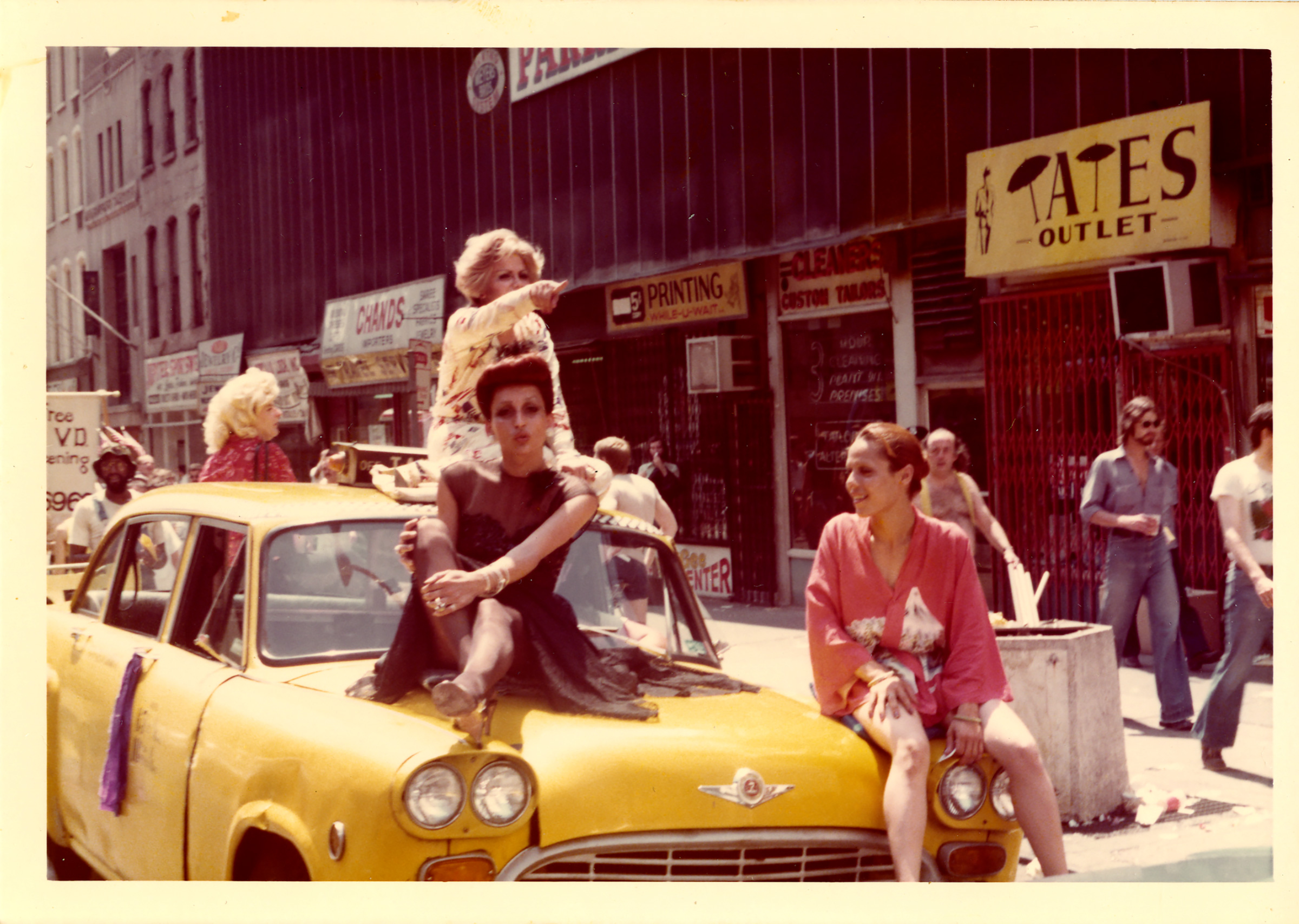 People perform on top of a yellow cab in 1976