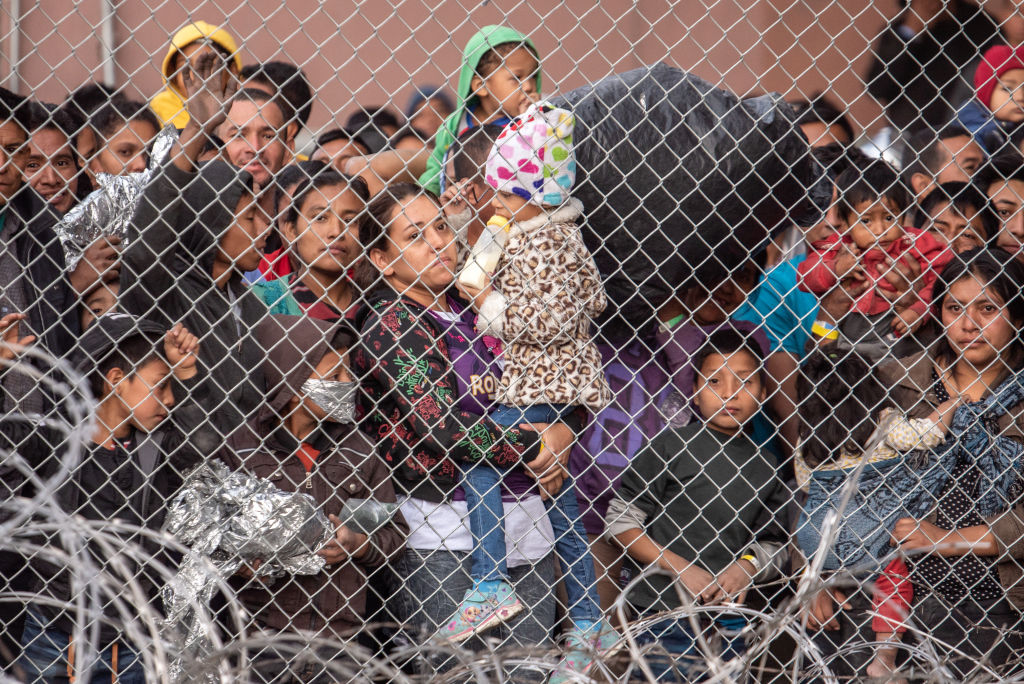 Migrants are gathered inside the fence of a makeshift detention center in El Paso, Texas on Wed. March 27, 2019.