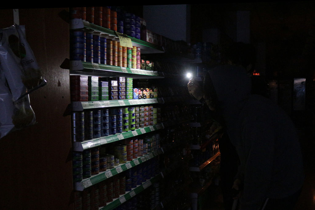 People illuminate the shelves of supermarkets with cell phones during  the massive outage in Buenos Aires, Argentina, on June 16, 2019.
