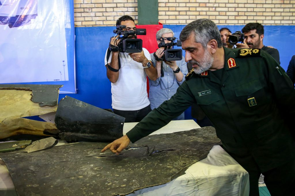 General Amir Ali Hajizadeh (R), Iran's Head of the Revolutionary Guard's aerospace division, speaks to media next to debris from a downed U.S. drone reportedly recovered within Iran's territorial waters and put on display by the Revolutionary Guard in the capital Tehran on June 21, 2019