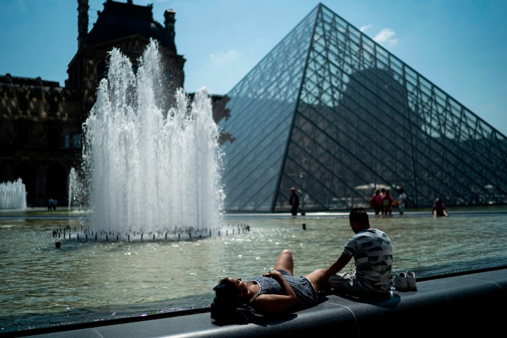 People sunbathe in front of the Louvre Pyramid during a heatwave in Paris on June 26, 2019.