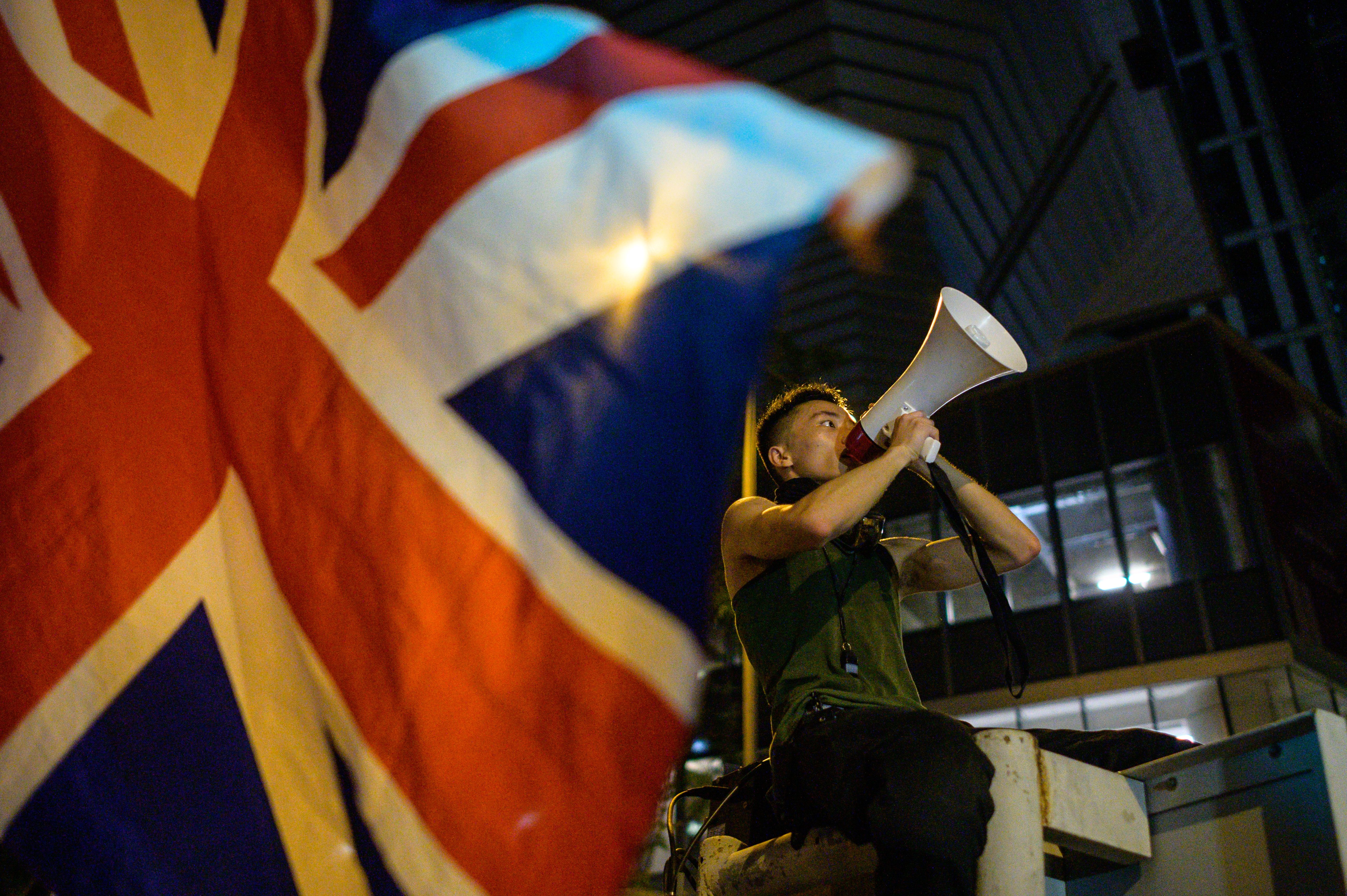 A British Union Jack flag is waved from the ground as a protester uses a loud hailer to speak outside the police headquarters in Hong Kong, early on June 27, 2019.