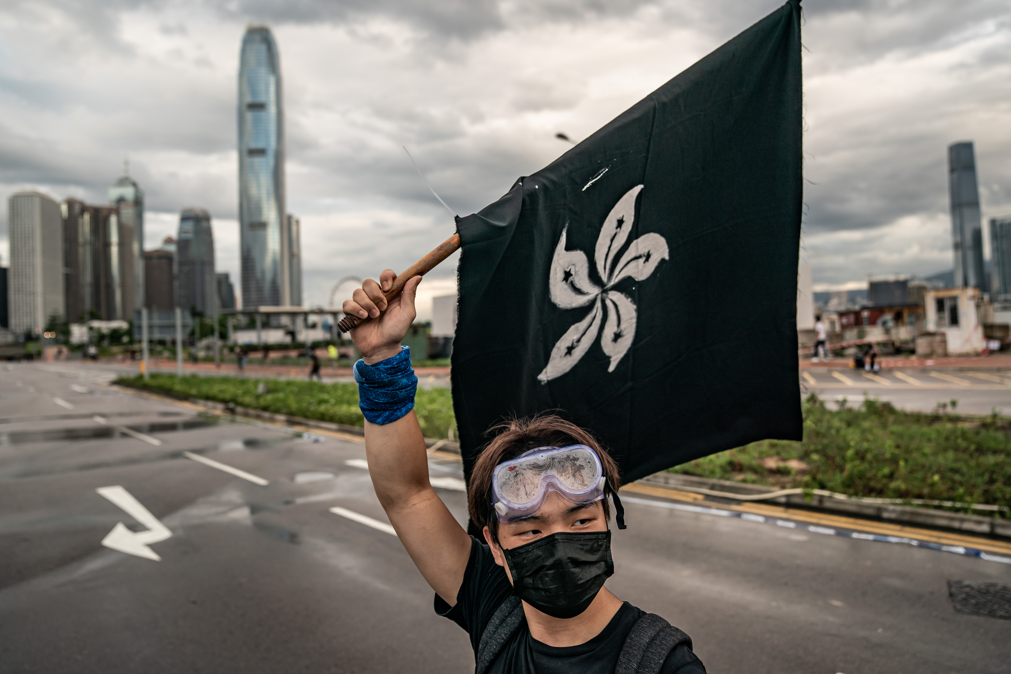 An anti-extradition protester waves a Black Bauhinia flag on a street outside the Legislative Council Complex ahead of the annual flag raising ceremony of 22nd anniversary of the city's handover from Britain to China on July 1, 2019 in Hong Kong, China.