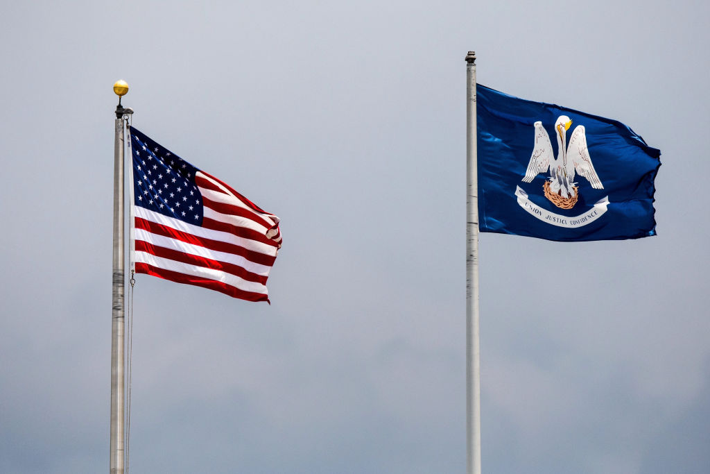 The American Flag and Louisiana State Flag waving in the breeze during the minor league game between the Colorado Springs Sky Sox and the New Orleans Baby Cakes on June 25, 2017 at Zephyr Field in Metairie, LA.