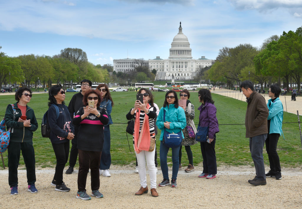 A group of Chinese tourists take photographs on the National Mall with the U.S. Capitol in the background.