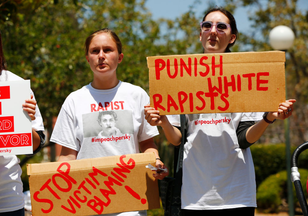 Zoe Gregozek and Hattie Dalzell, left to right, attend a protest calling for the impeachment of Santa Clara County Superior Court Judge Aaron Persky at the Old Courthouse in San Jose, California on Monday, August 1, 2016. Upset by the light jail sentence he gave former Stanford student Brock Turner.
