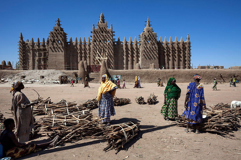 In front of the Great Mosque of Djenne on January 22, 2010 in Djenne, Mopti region, Mali. The Mosque is located in the old town of Djenné, World Heritage Site by UNESCO, on the flood plain of the Bani River