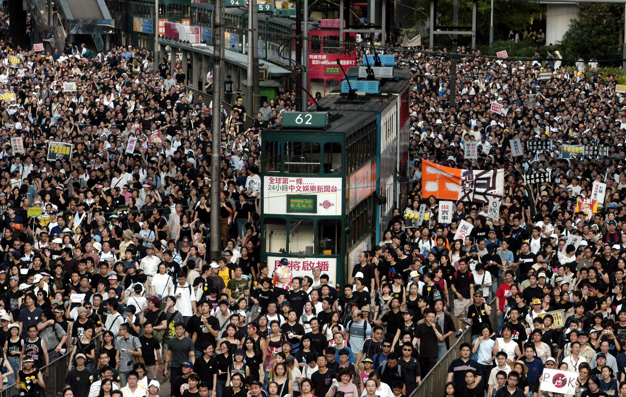 Tens of thousands of people pack a Hong Kong street while marching to Hong Kong government headquarters on July 1, 2003.