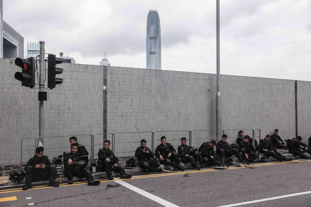 Police rest on a street during a rally near the government headquarters on June 12.