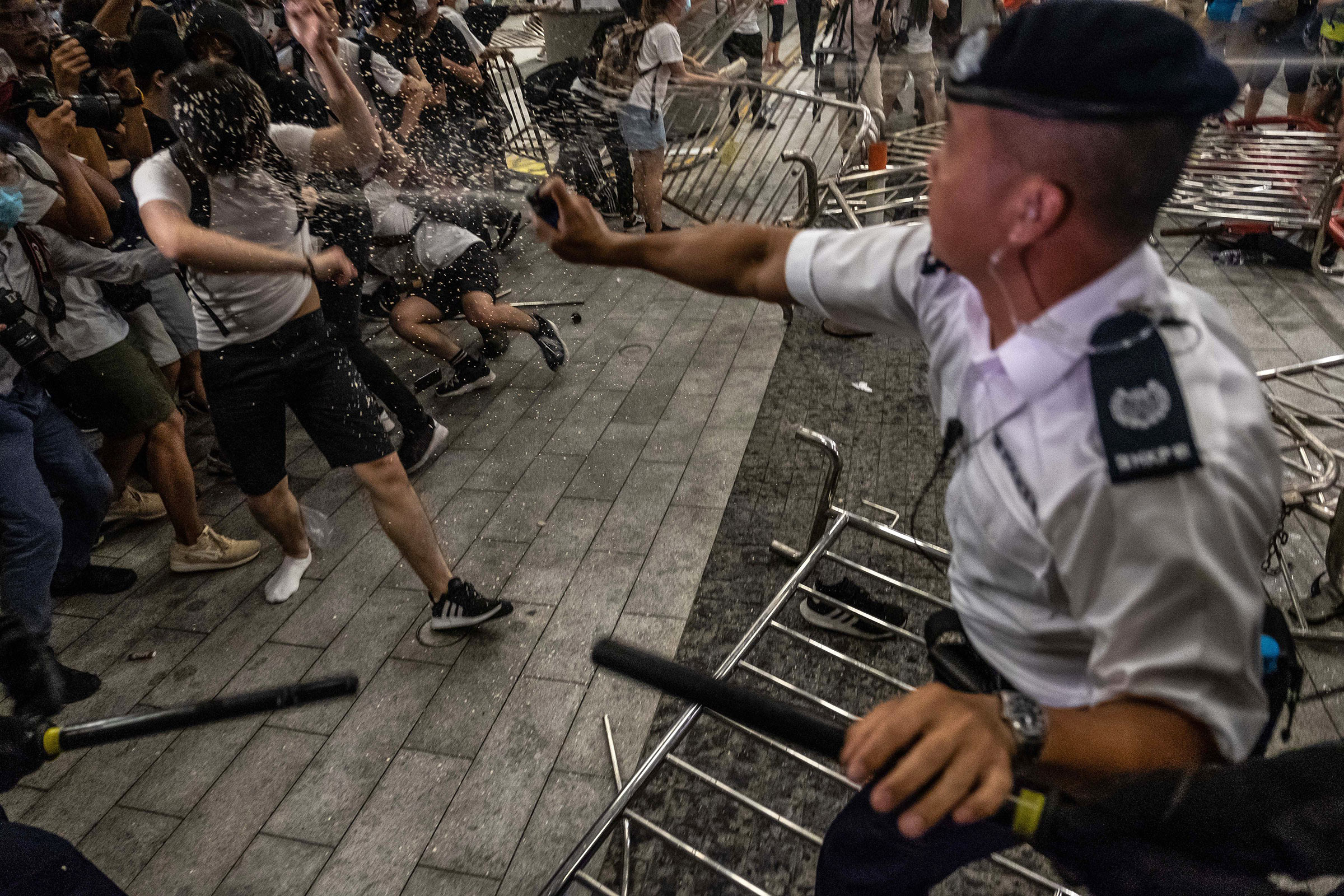A police officer pepper-sprays demonstrators during a protest against the extradition law proposal on June 10.